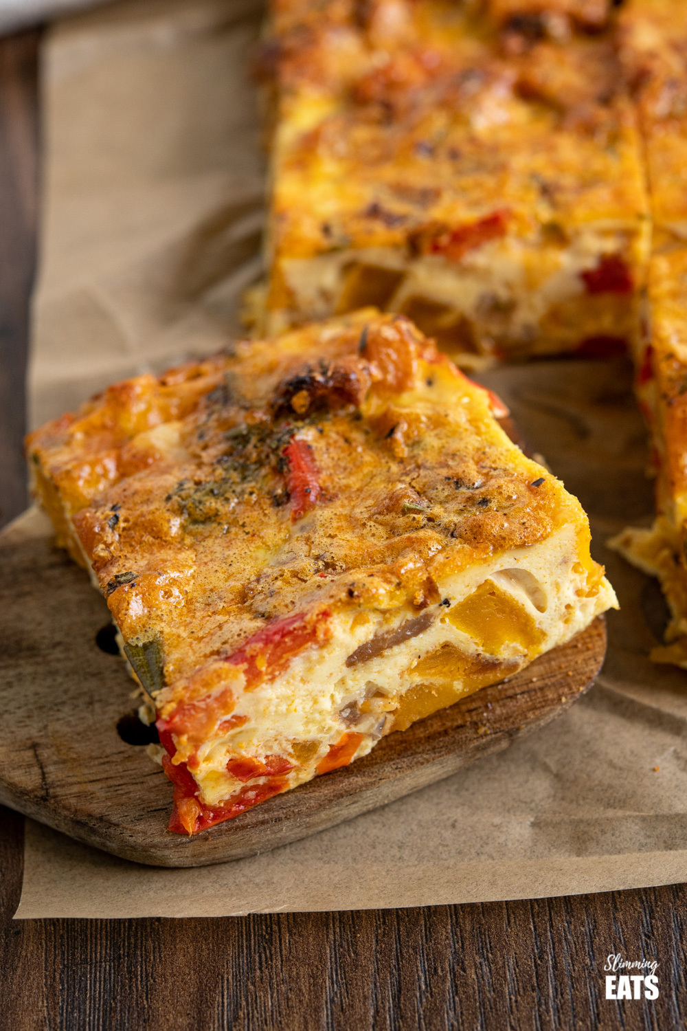 close up of slice of roasted butternut squash and red pepper quiche on parchment paper