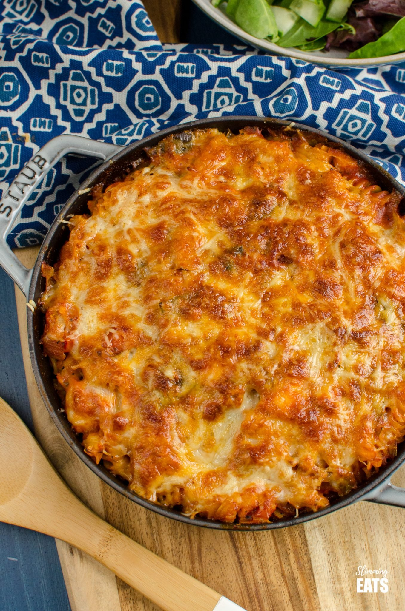 Salmon and Leek Pasta Bake is grey cast iron staub skillet with bowl of salad in background