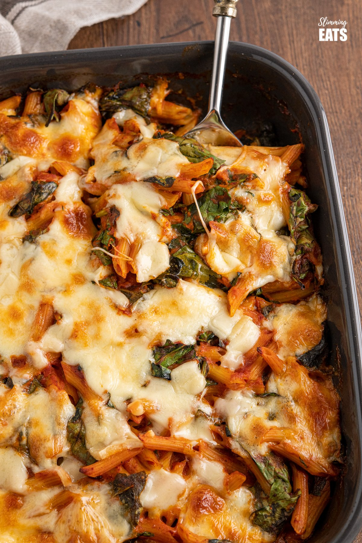 close up of spinach pasta bake with spoon in dark grey oven dish