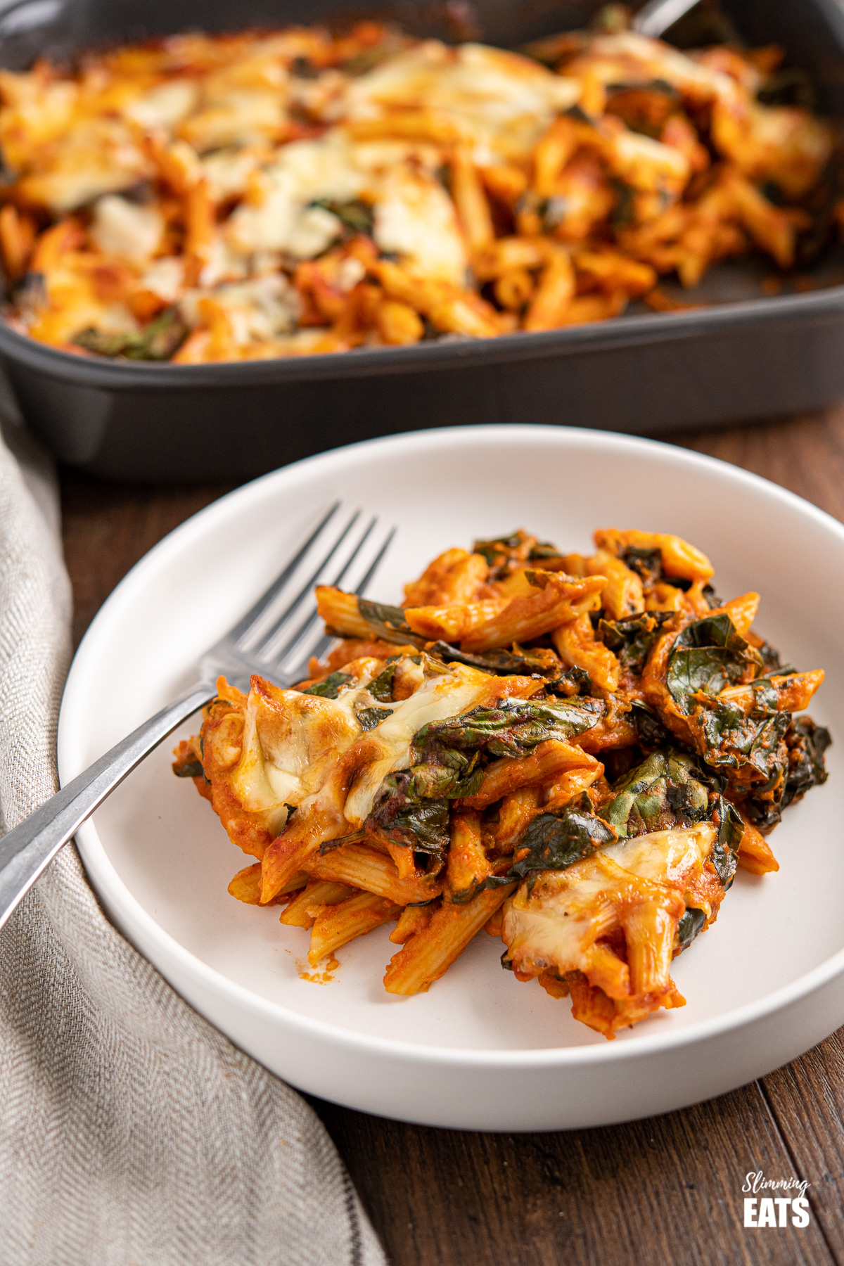 white plate with a serving of spinach pasta bake, oven dish in background