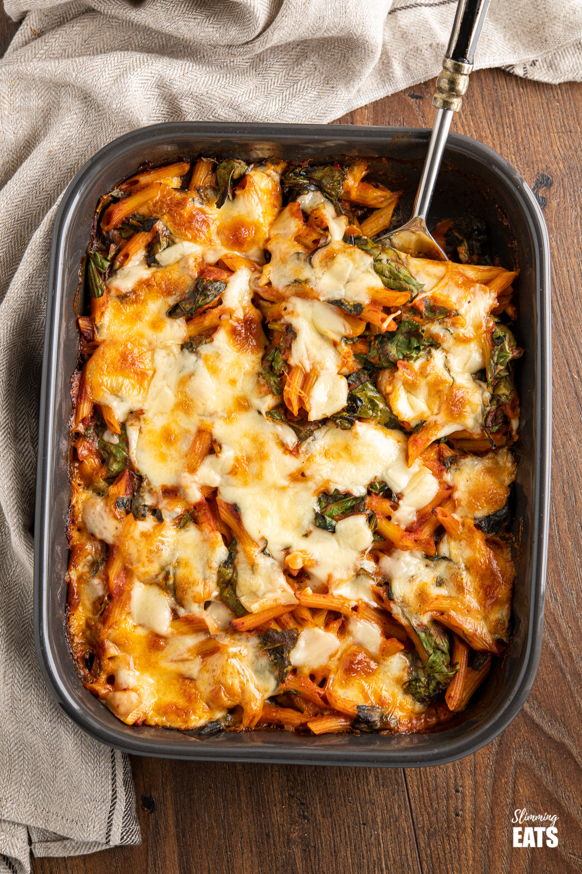 spinach pasta baked in grey oven dish on wooden board