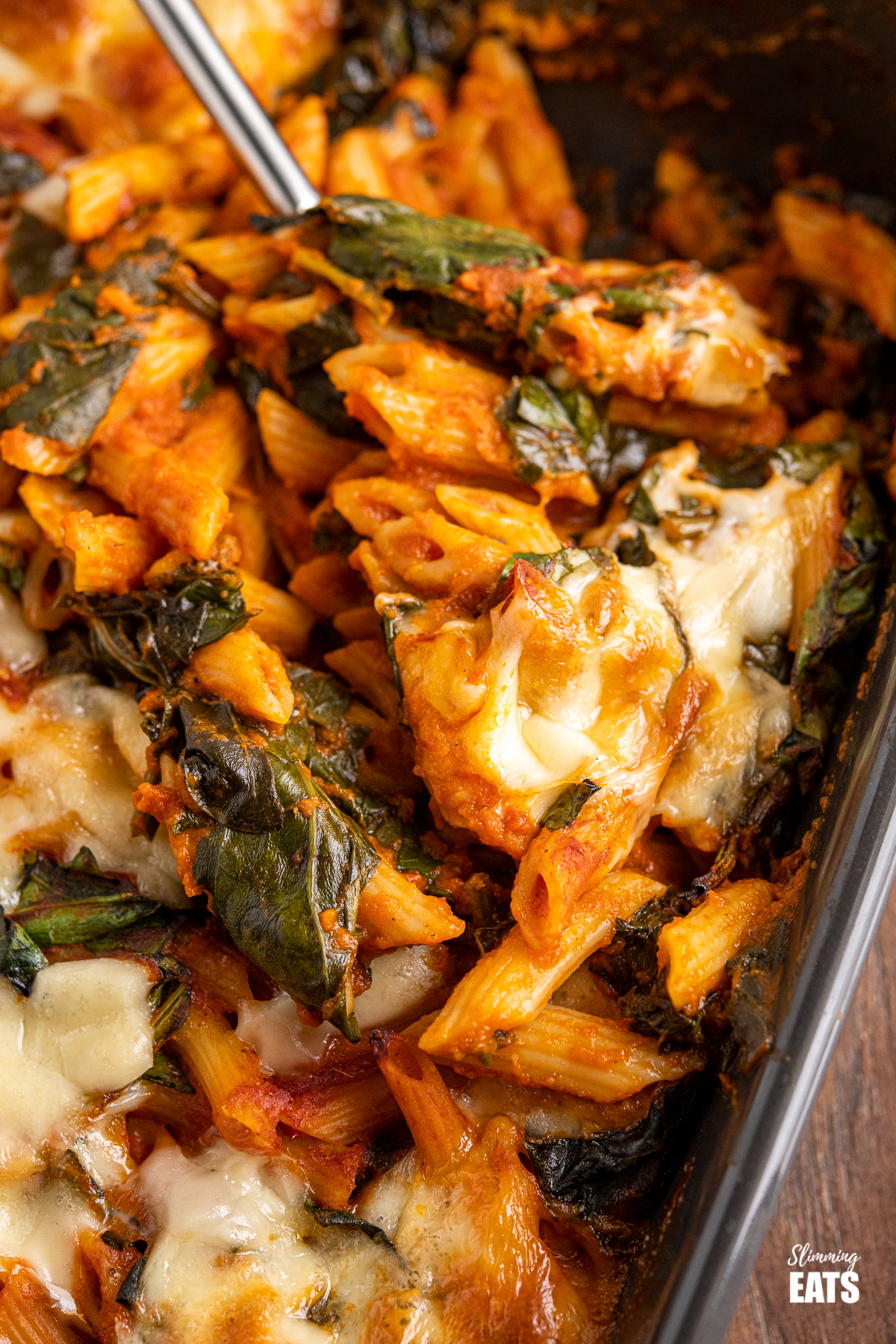 spoon dishing up spinach pasta bake from dark grey oven dish
