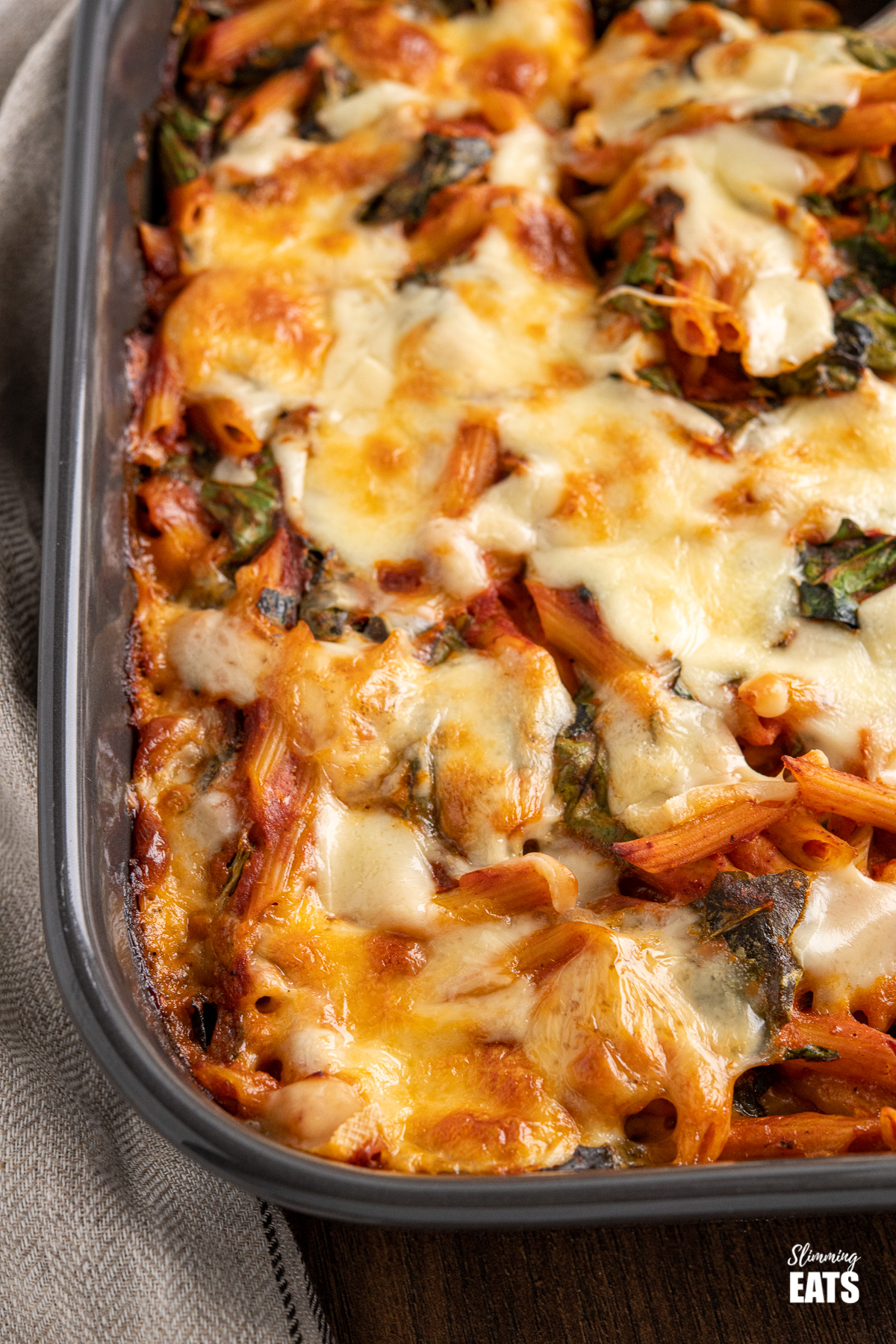 close up of spinach pasta bake in dark grey oven dish