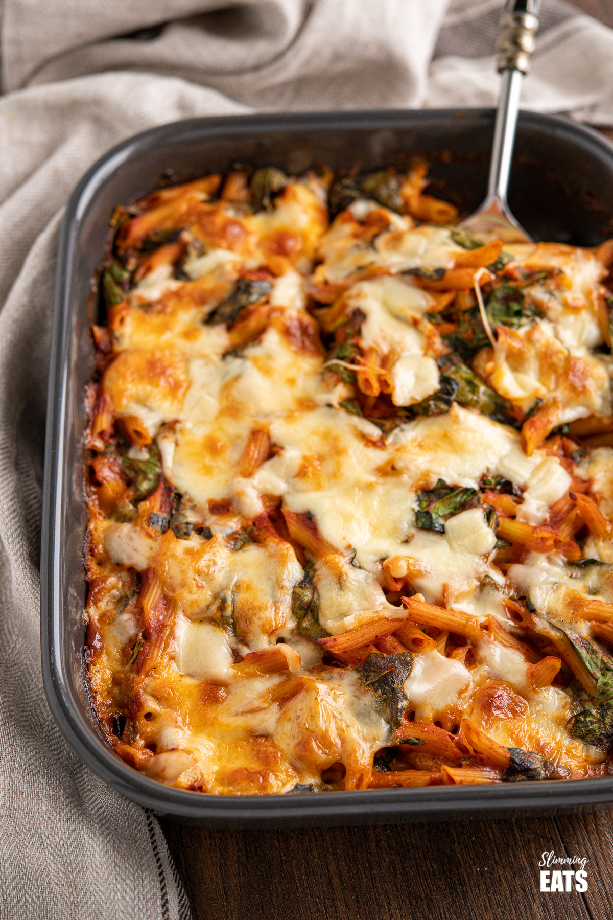 spinach pasta bake with spoon in dark grey oven dish