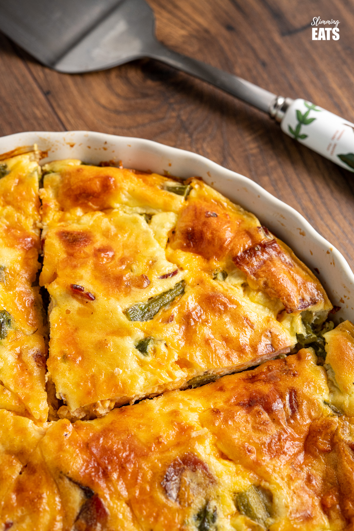 close up of slice of Crustless Asparagus and Bacon Quiche in flan dish with spatula on wooden board