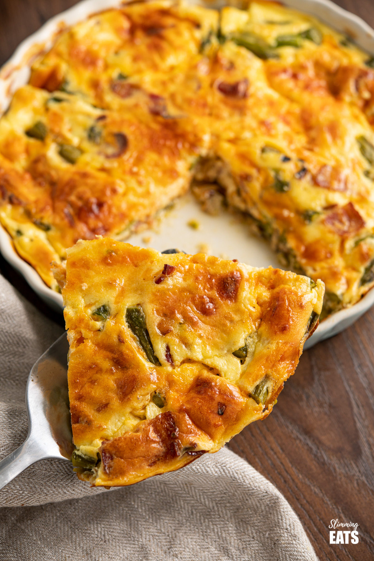 slice of Crustless Asparagus and Bacon Quiche on spatula from flan dish