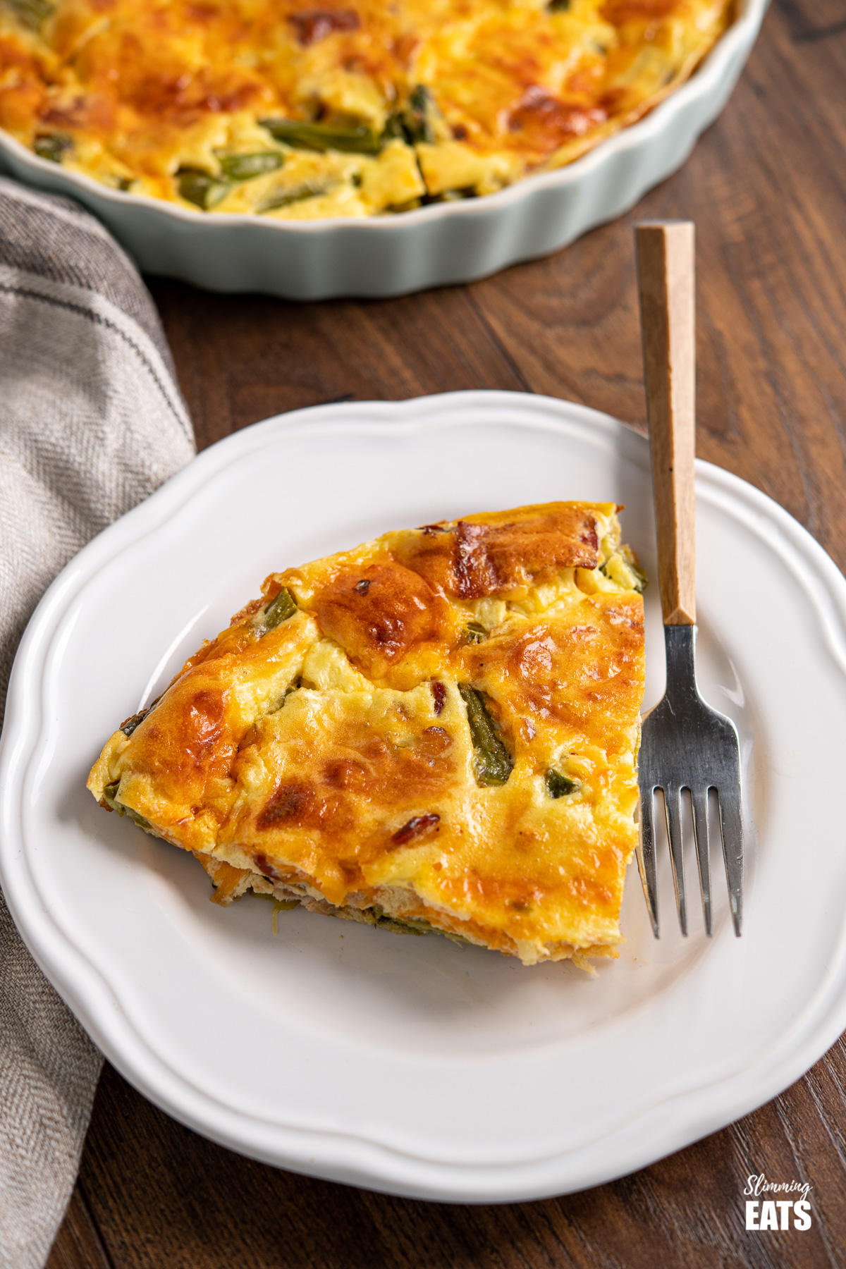 slice of Crustless Asparagus and Bacon Quiche on white plate with wooden handles fork.