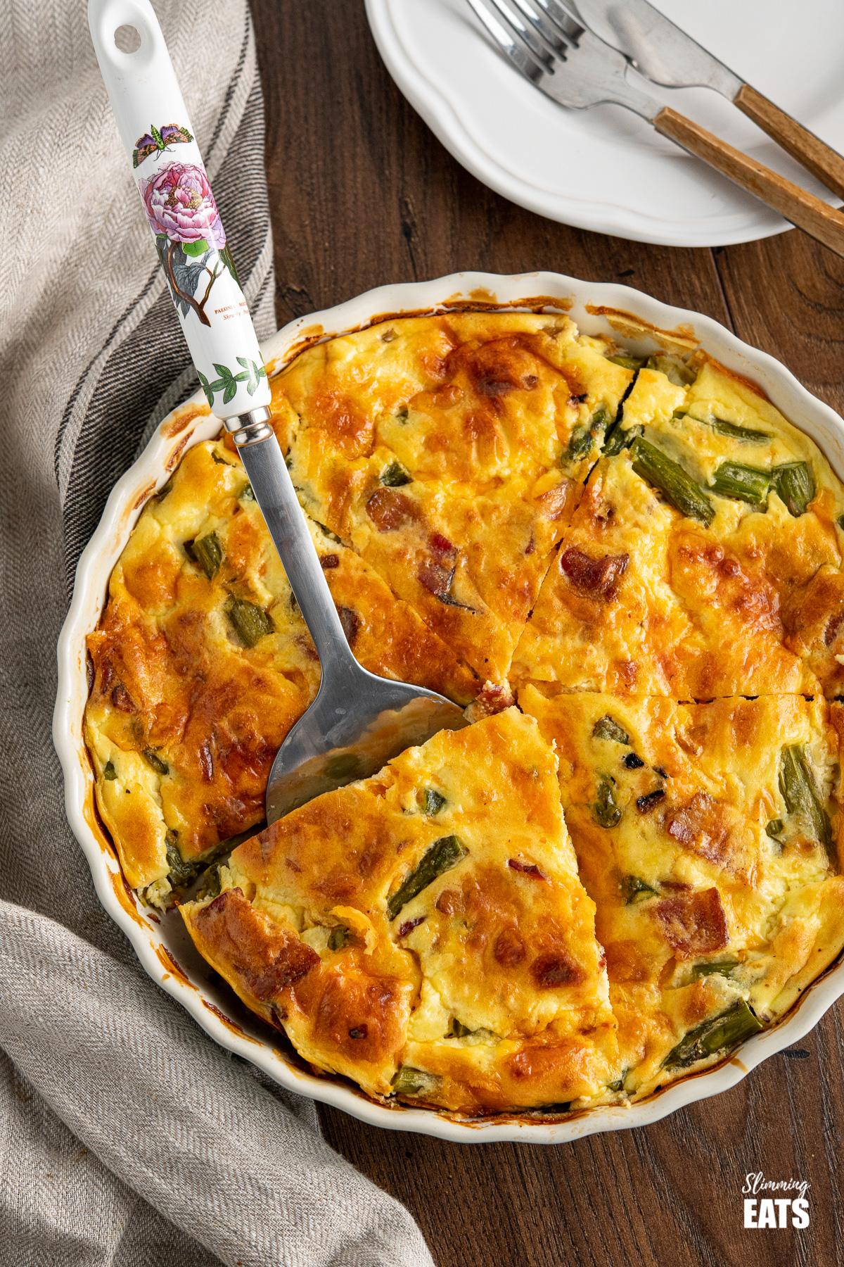 Crustless Asparagus and Bacon Quiche in flan dish with spatula on wooden board