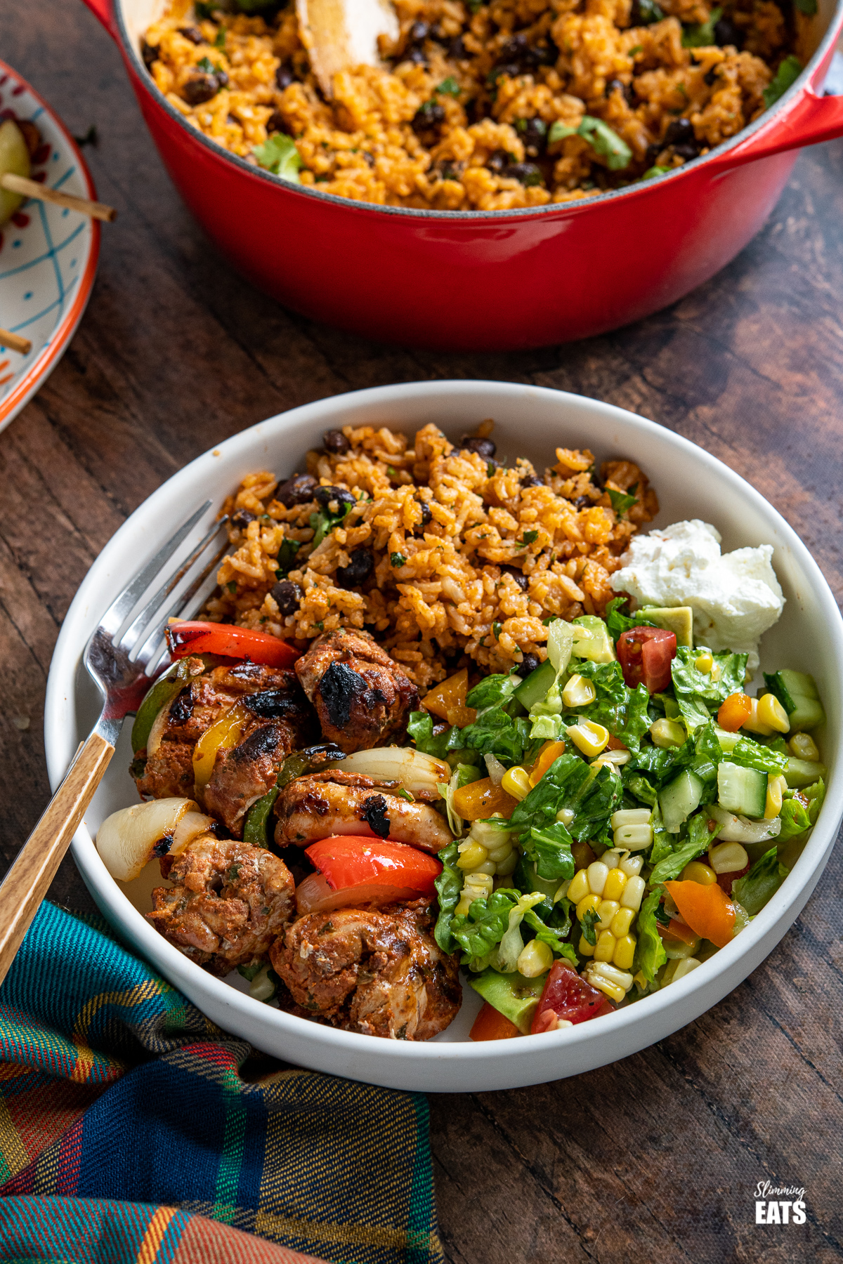 mexican chicken in a grey brown bowl with rice, sour cream and salad