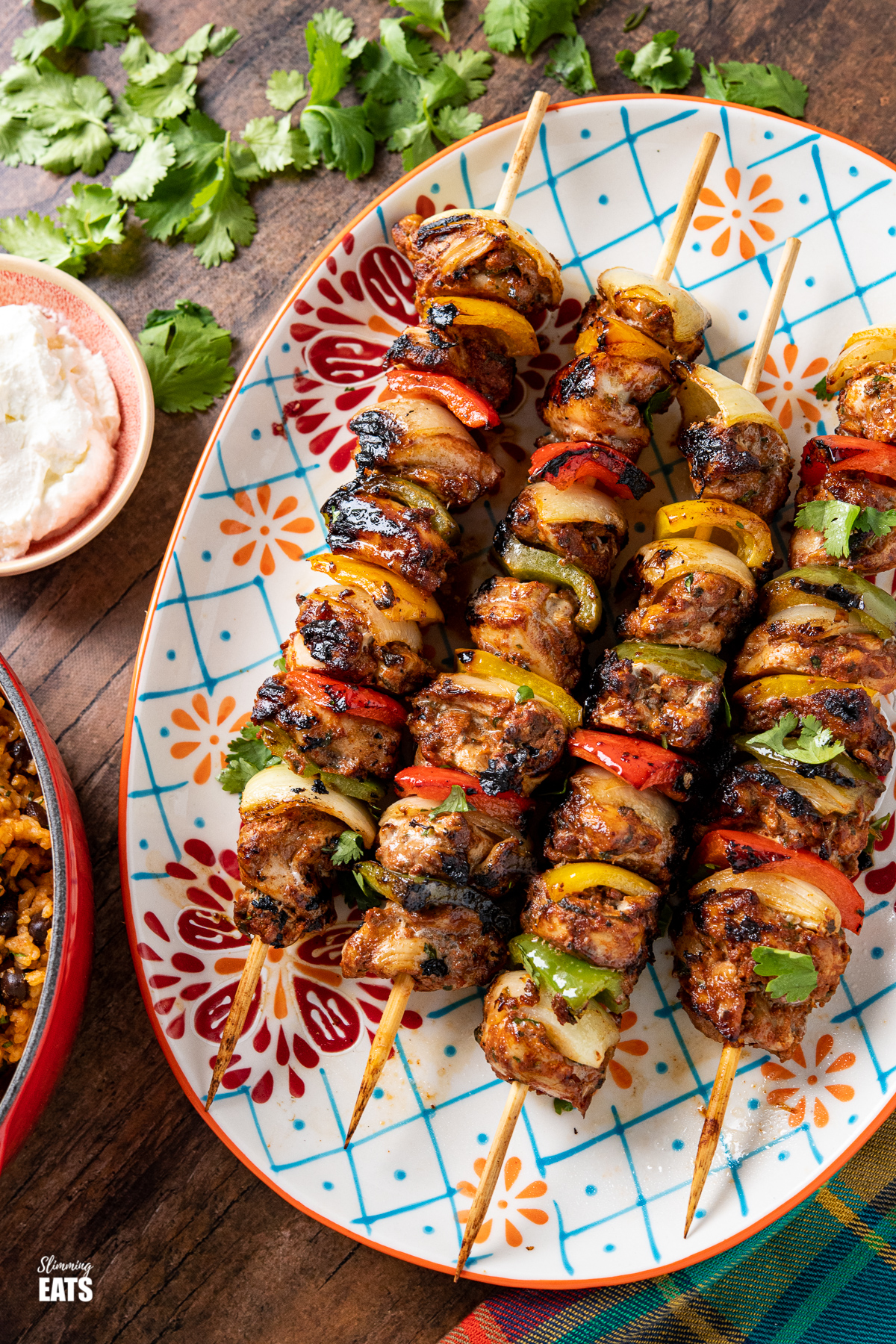 close up of chicken skewers on a oval patterned plate