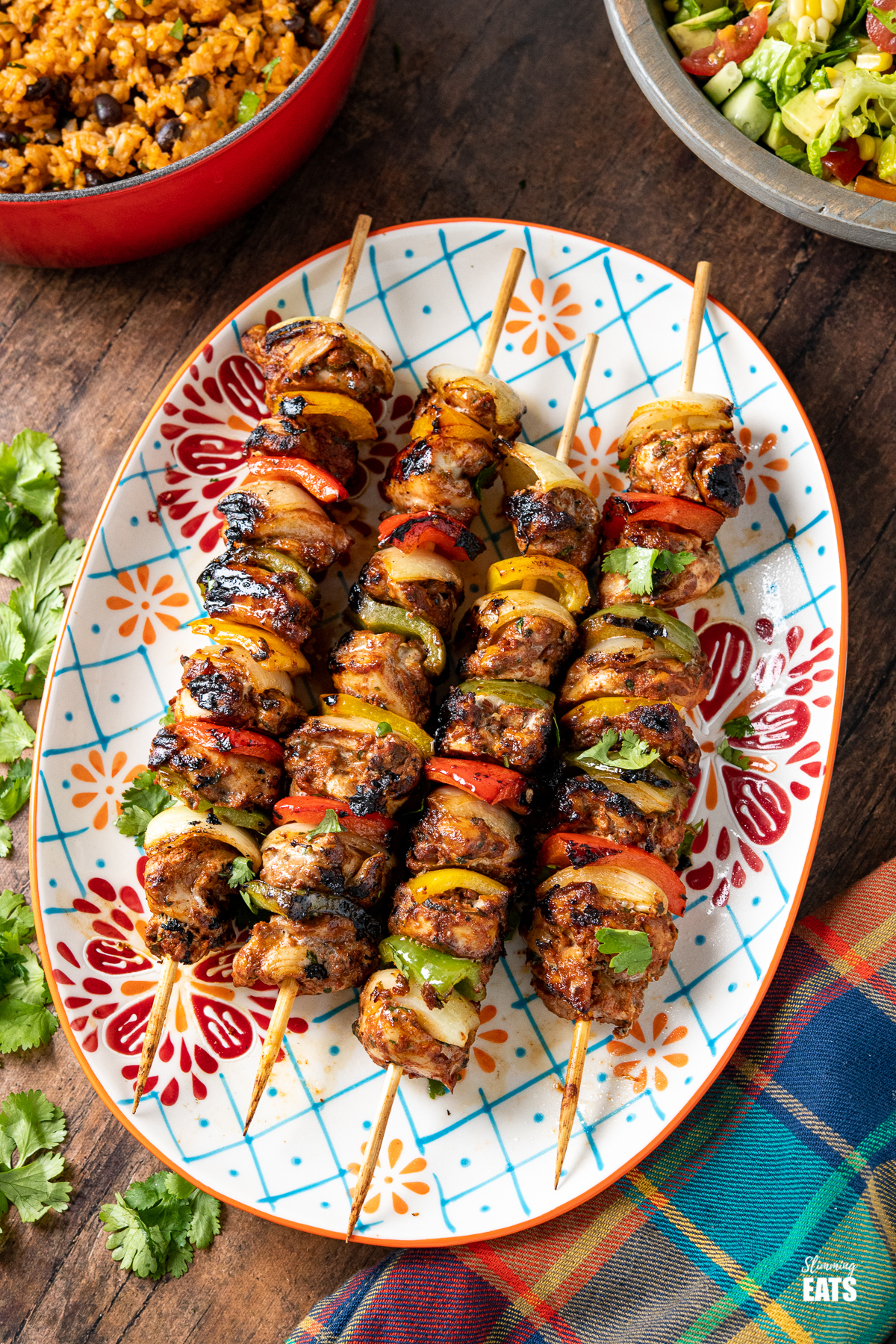 chicken skewers on a oval patterned plate with a pan or rice and bowl of salad in background