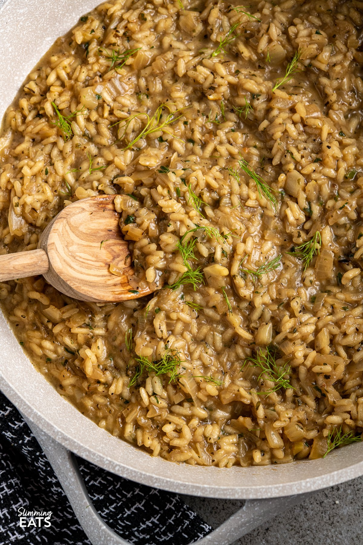 close up of Fennel and Sweet Onion Risotto in non stick grey brown frying pan with olive wood spoon