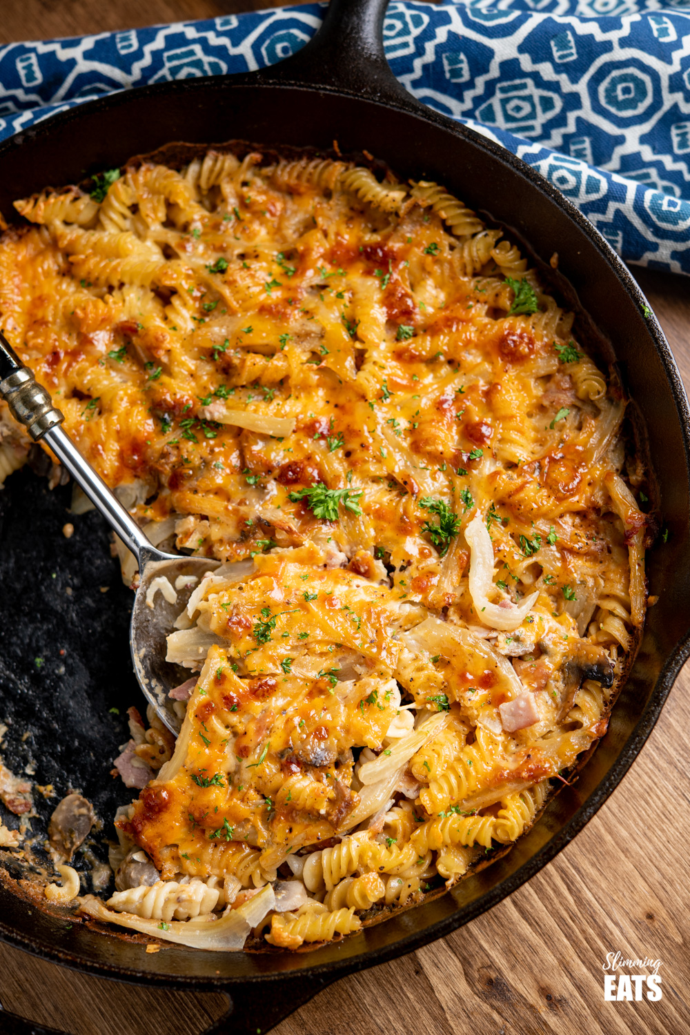 Bacon, Fennel and Mushroom Pasta Bake in a cast iron skillet on wooden board