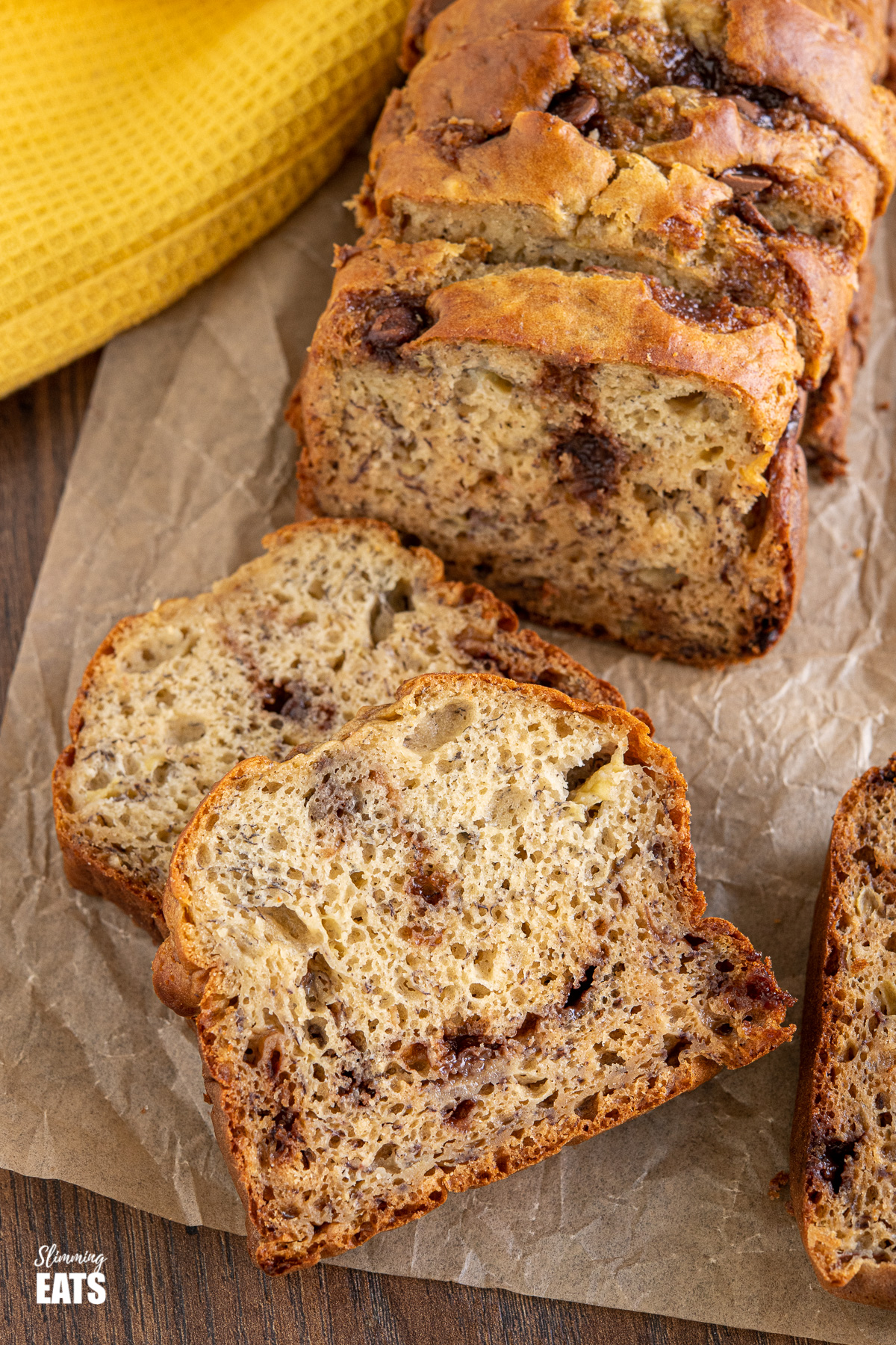 Sliced Healthy Banana and Chocolate Chip Loaf on parchment paper with yellow tea towel