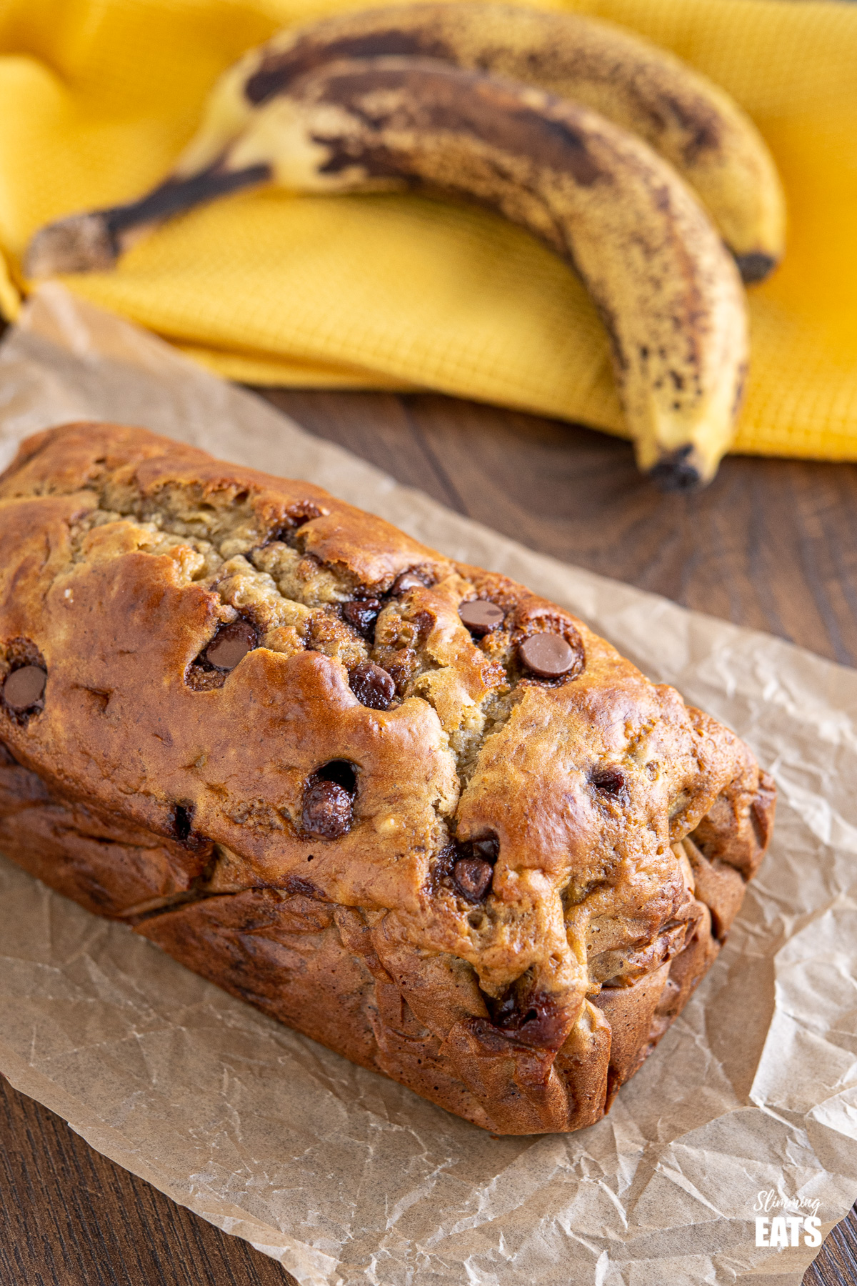 Healthy Banana and Chocolate Chip Loaf on parchment paper with ripe bananas in background on yellow tea towel