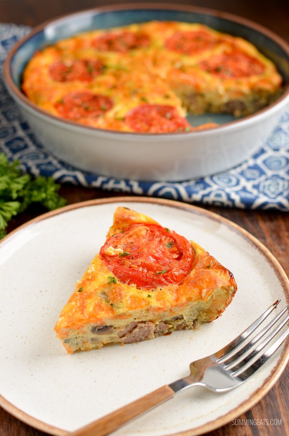 slice of breakfast quiche on a white plate with fork