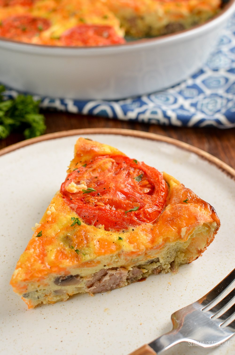 slice of breakfast quiche topped with tomato slice on a white plate