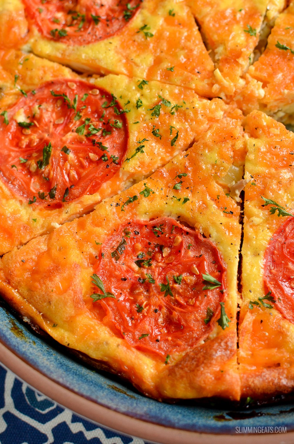 close up of sliced breakfast quiche topped with tomato slices