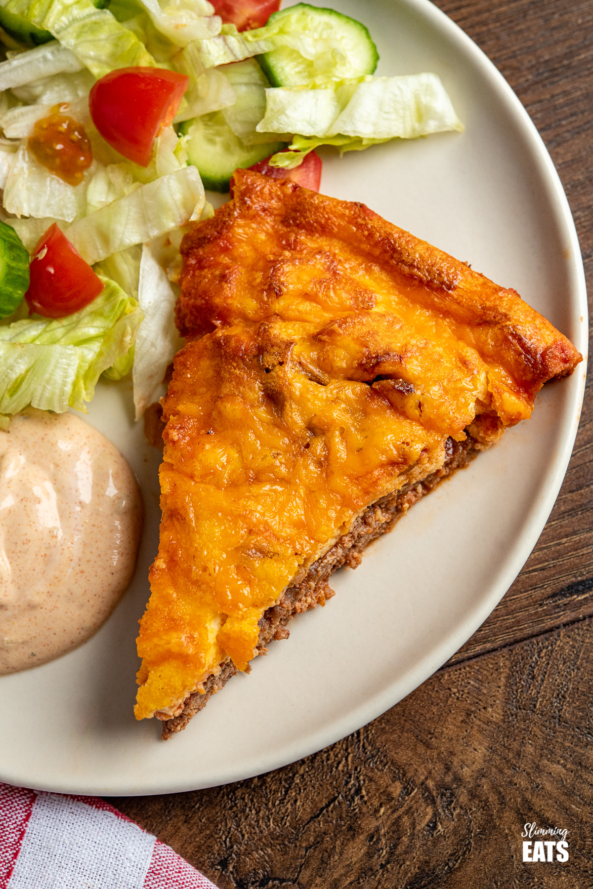 close up of slice of cheeseburger quiche on a plate with burger sauce and salad