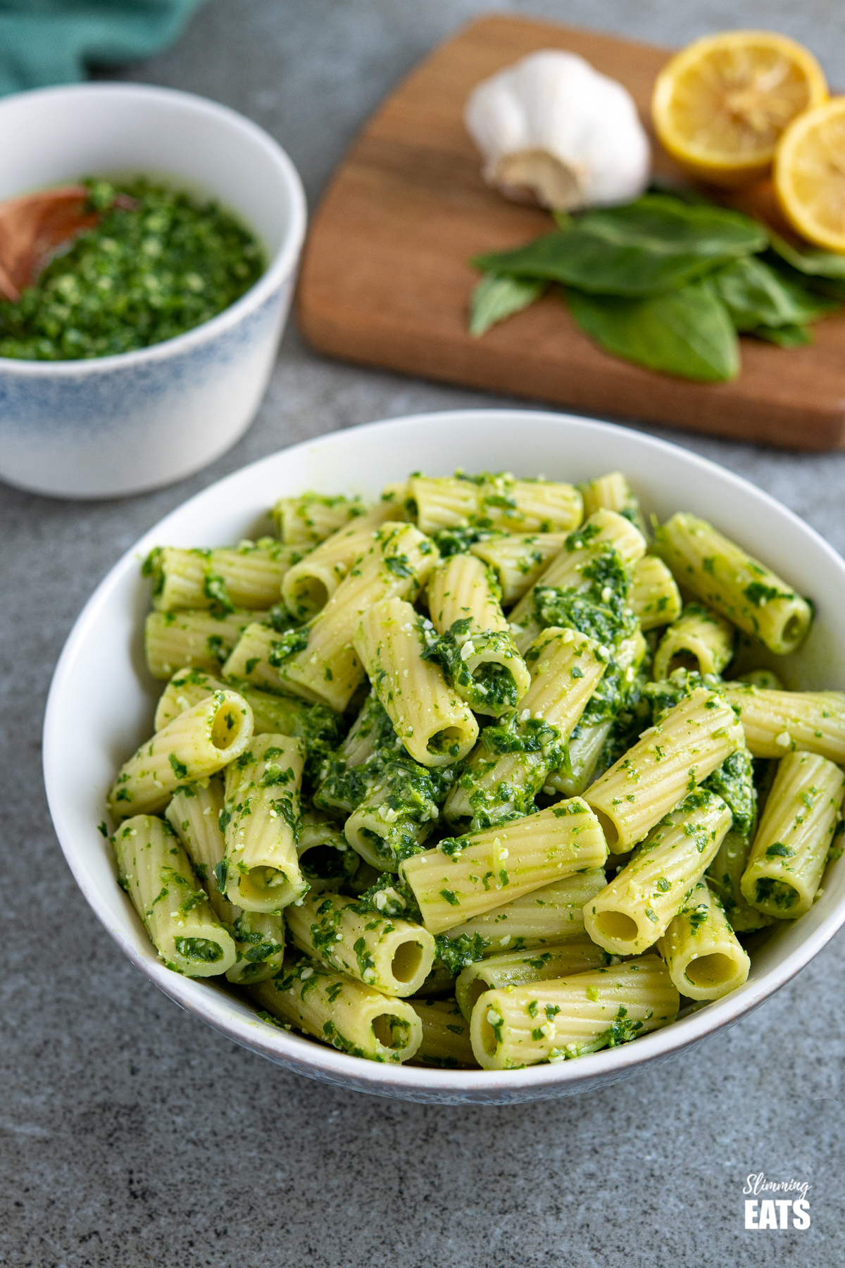 skinny pesto on cooked pasted in a white bowl with basil, lemon and garlic, and bowl of homemade pesto behind