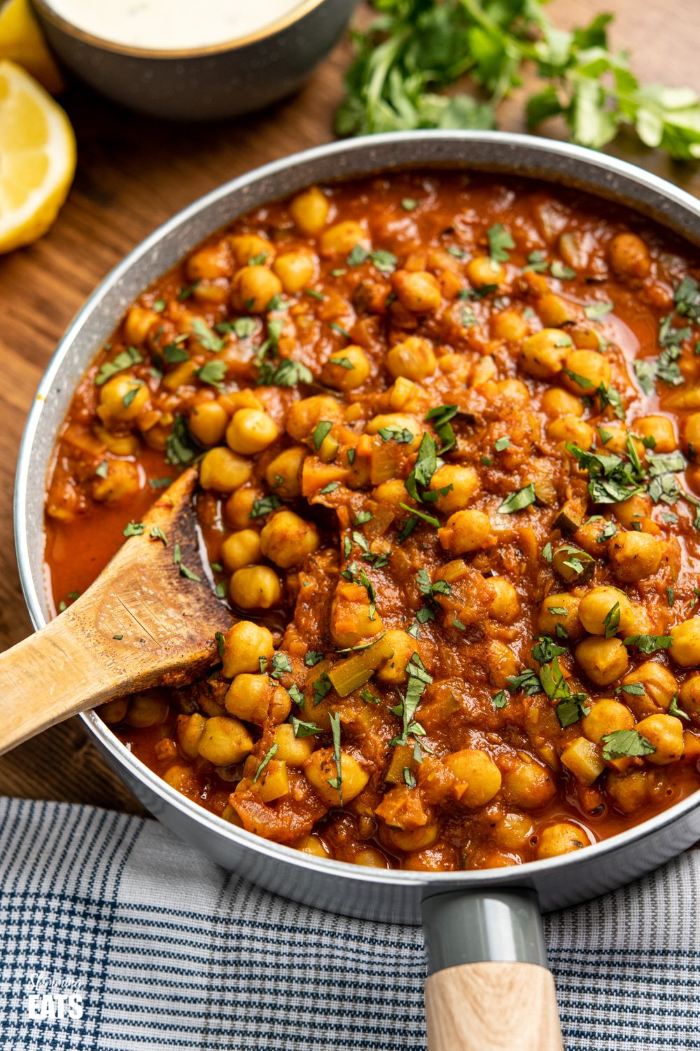 Chana Masala in a pan with wooden spoon, coriander and lemon wedges in the background on a wooden board.