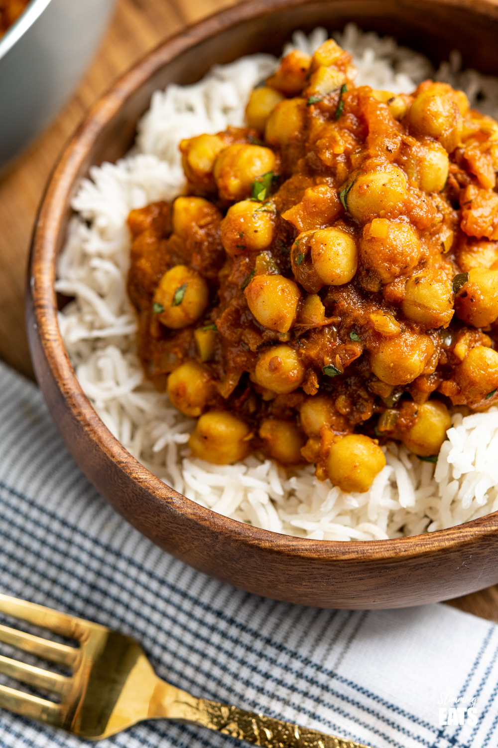 close up of Chana Masala in wooden bowl over white rice