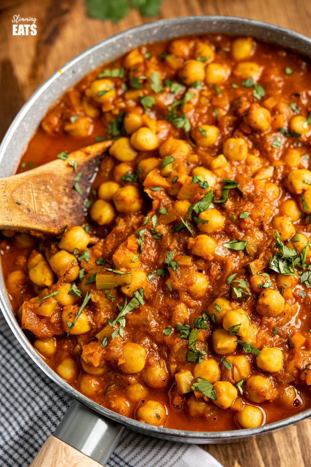 close up of Chana Masala in grey pan with wooden spoon of board