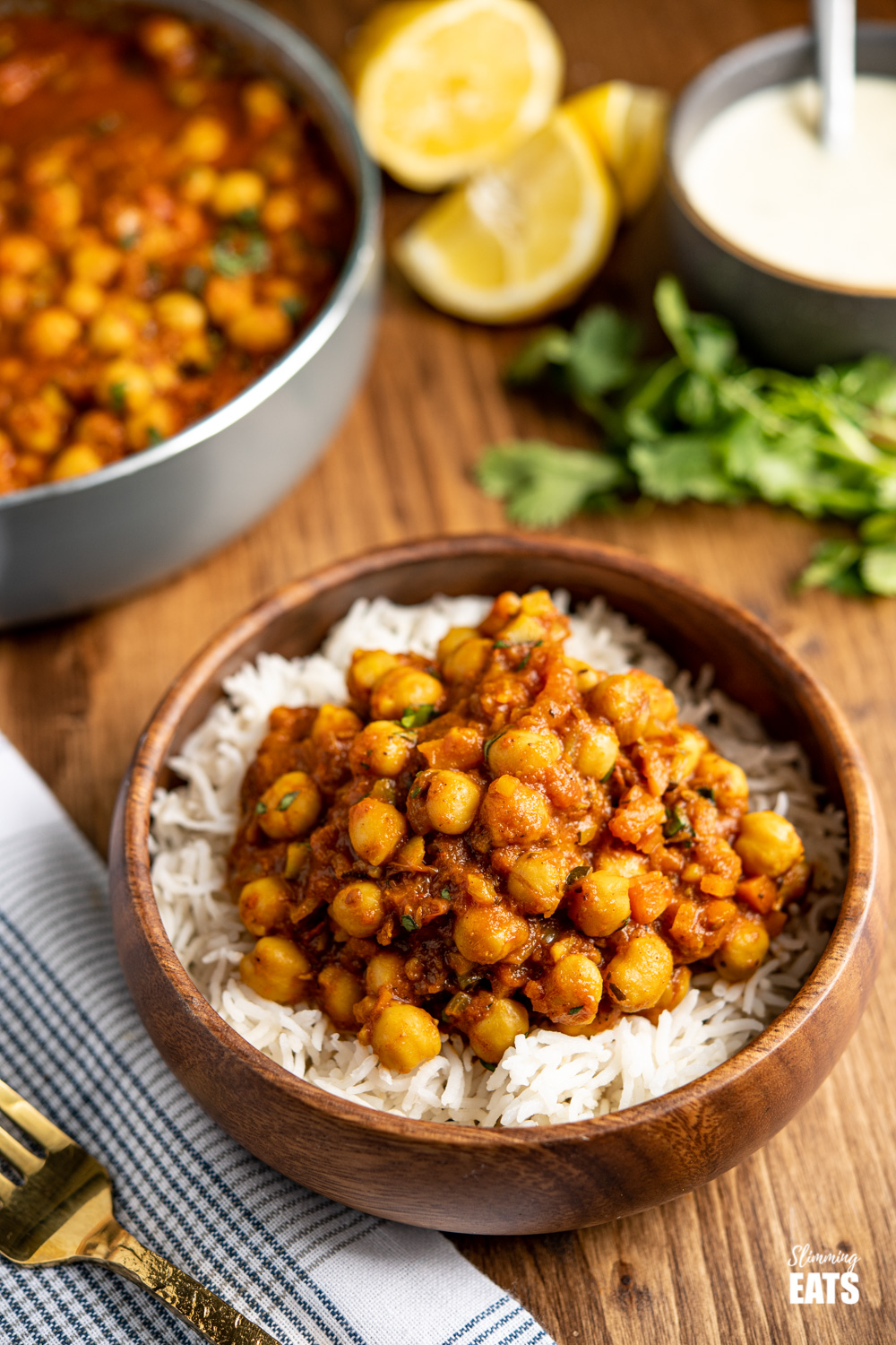 chana masala over white rice in a wooden bamboo bowl with gold fork to the left