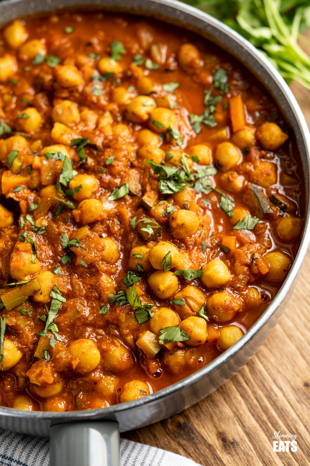 Chana Masala close up in grey frying pan on wooden board