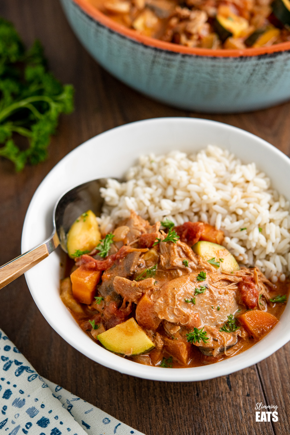 slow cooker creamy tomato and turkey casserole in white bowl with rice and wooden handled spoon