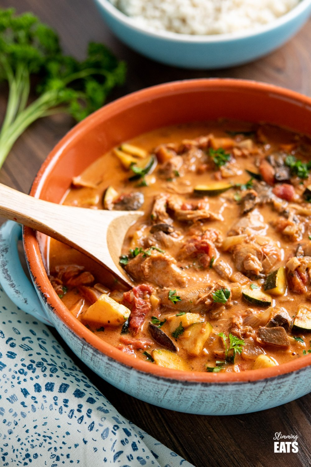 slow cooker creamy tomato and turkey casserole in ceramic blue dish with wooden spoon