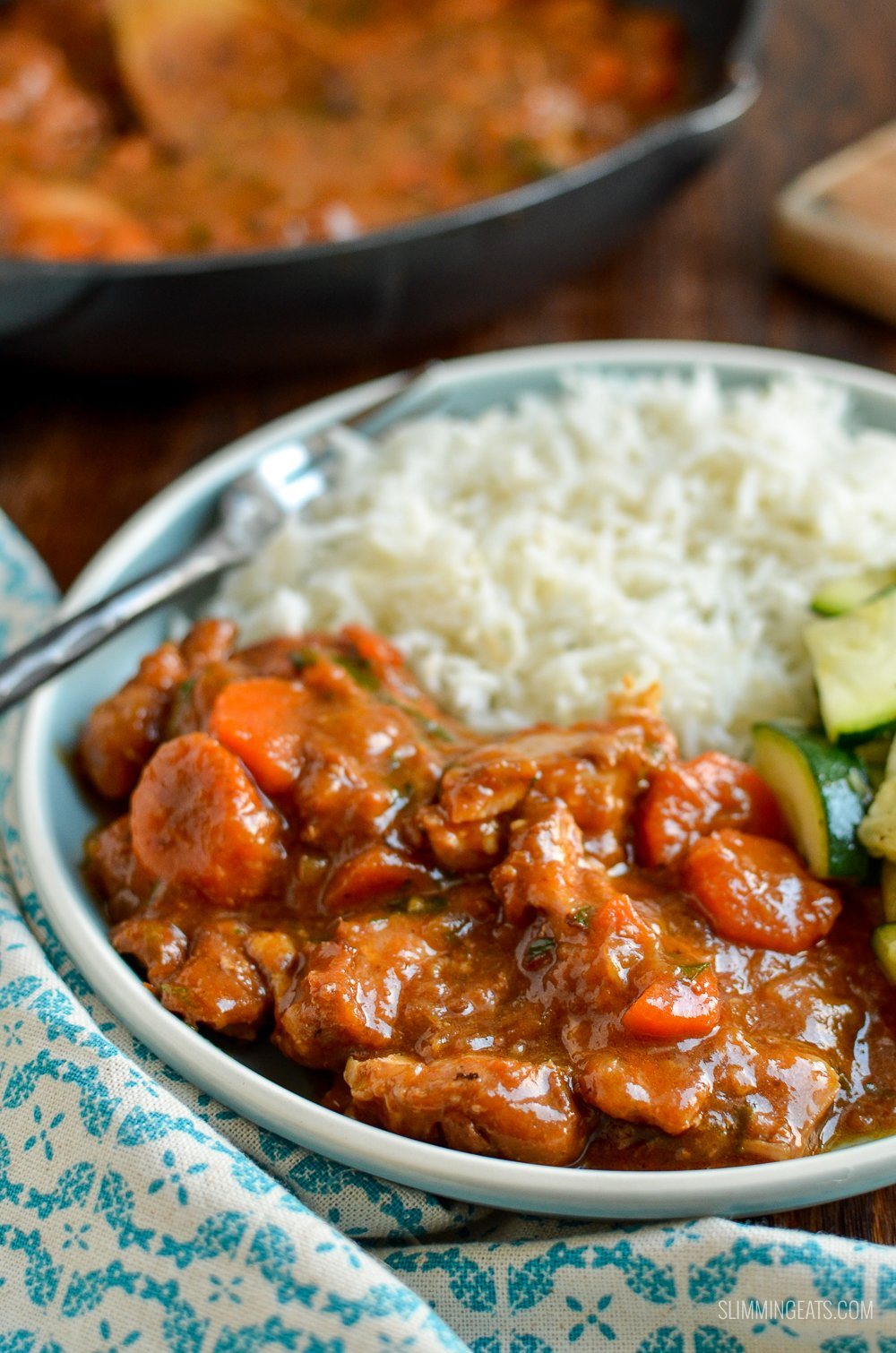 spicy ginger chicken on blue plate with sautéed zucchini and rice