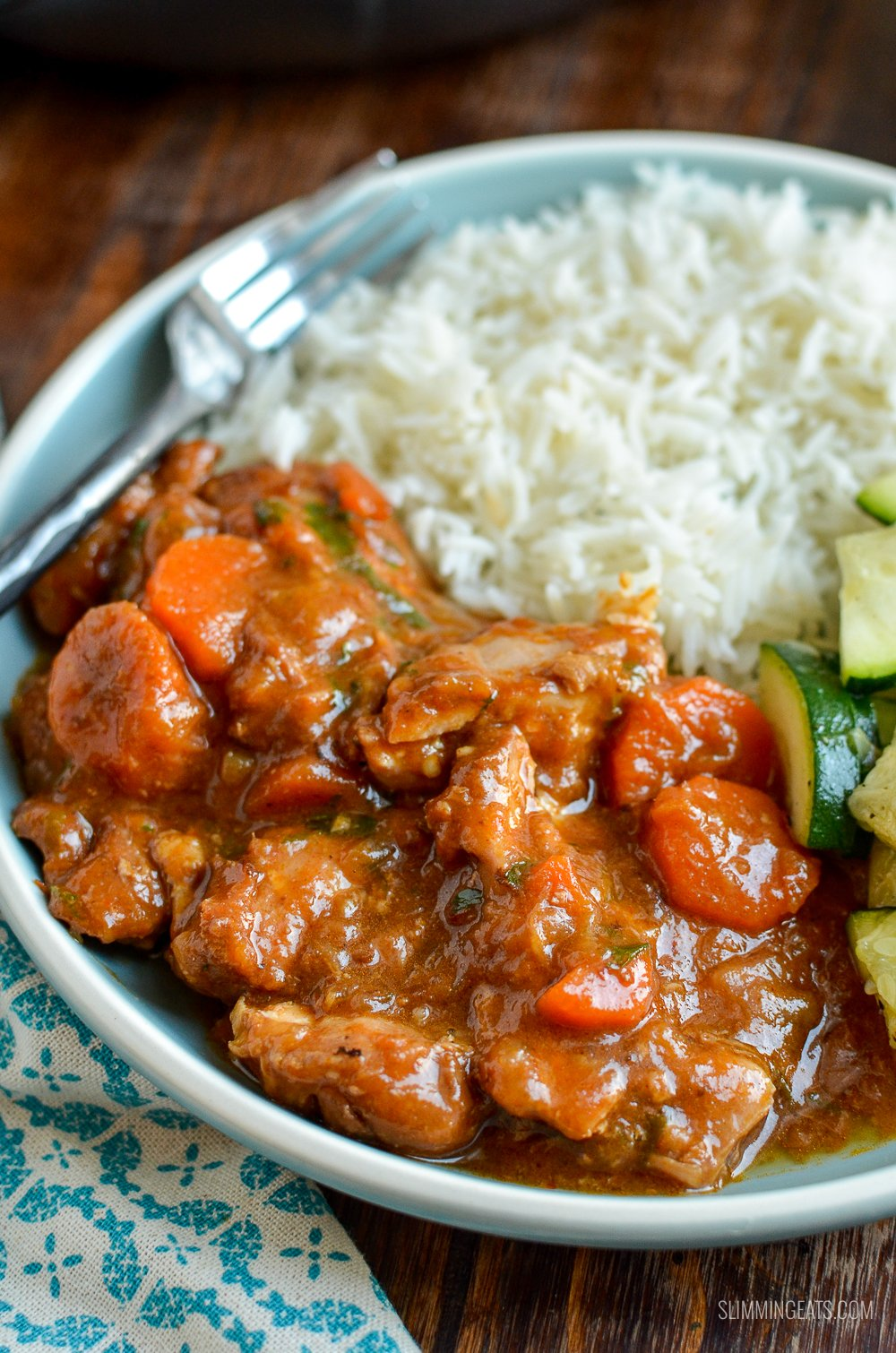 close up of spicy ginger chicken on blue plate with white rice