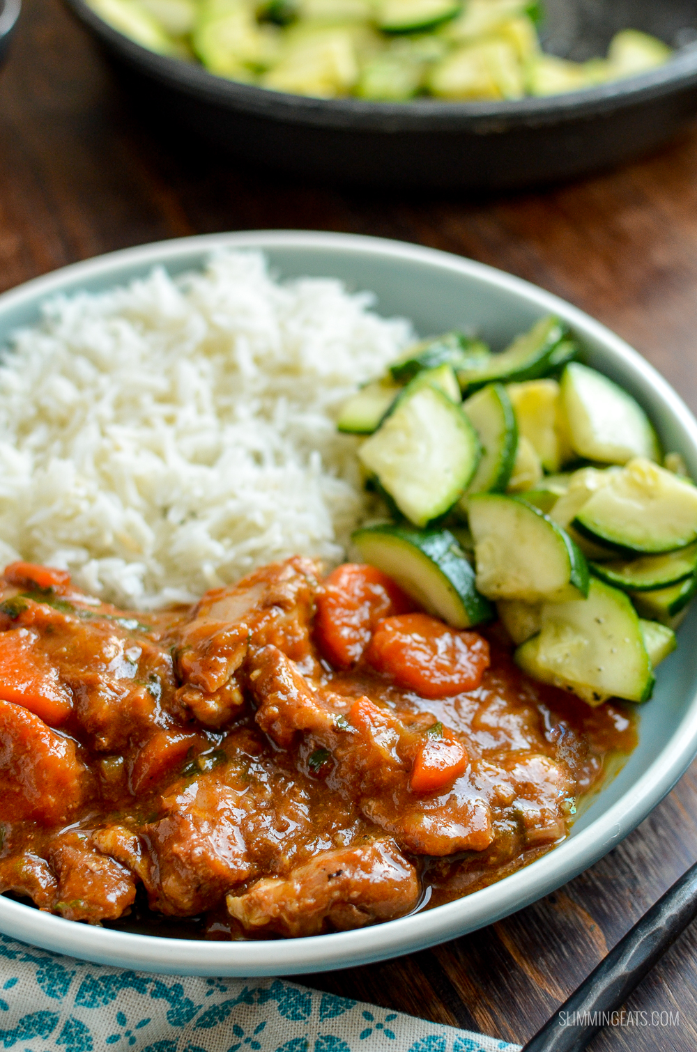 spicy ginger chicken on blue plate with zucchini and rice on wooden board