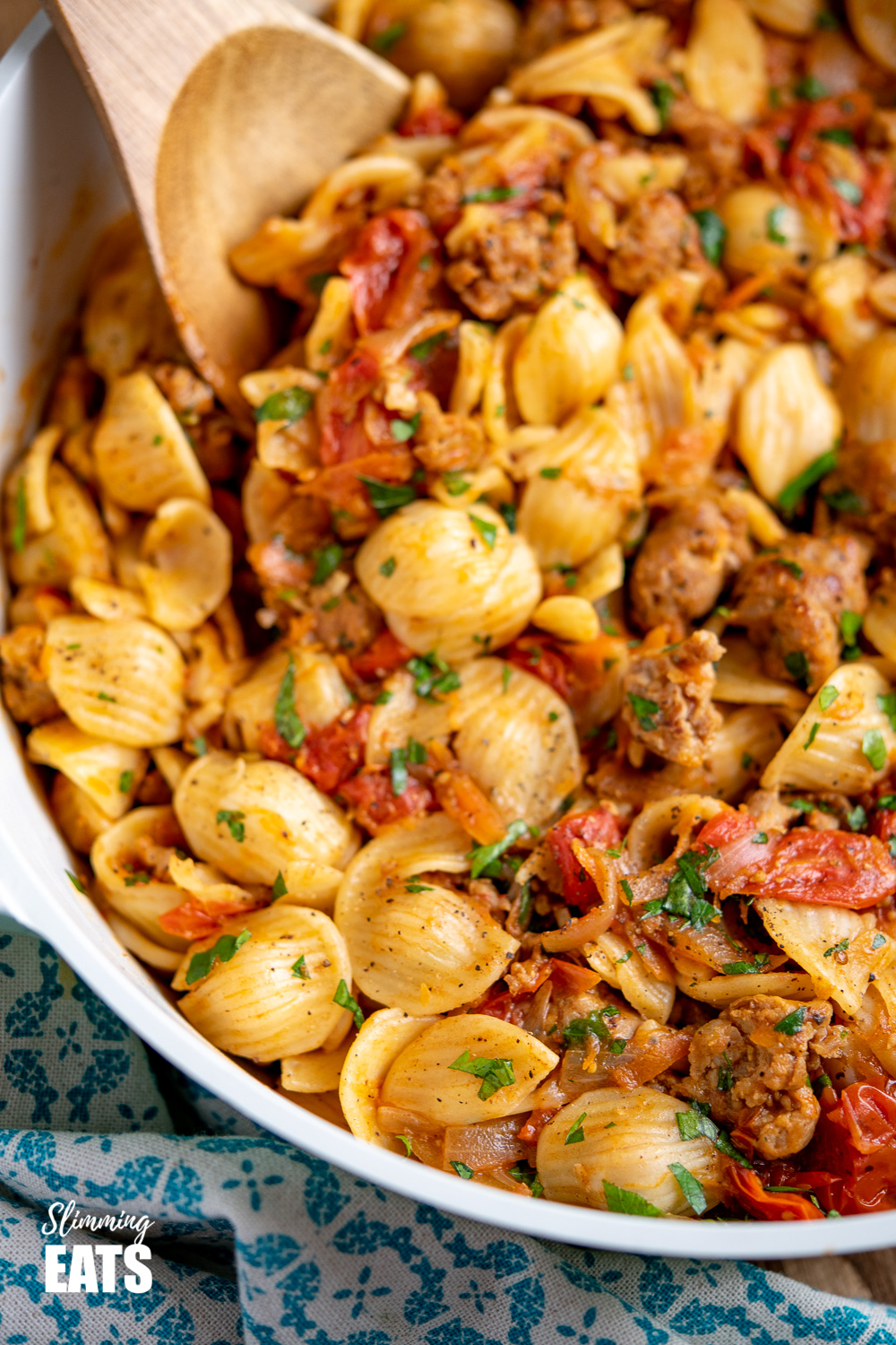 Sausage, Balsamic Tomatoes and Onion with Orecchiette close up in pan with wooden spoon