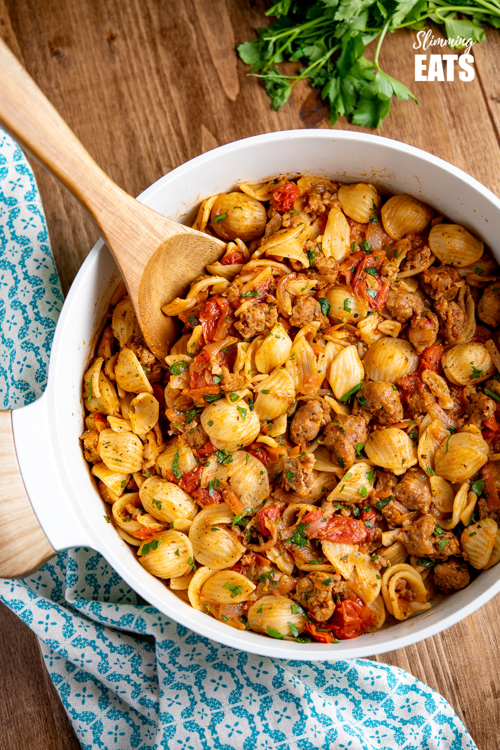 Sausage, Balsamic Tomatoes and Onion with Orecchiette in pan ceramic pan with wooden spoon
