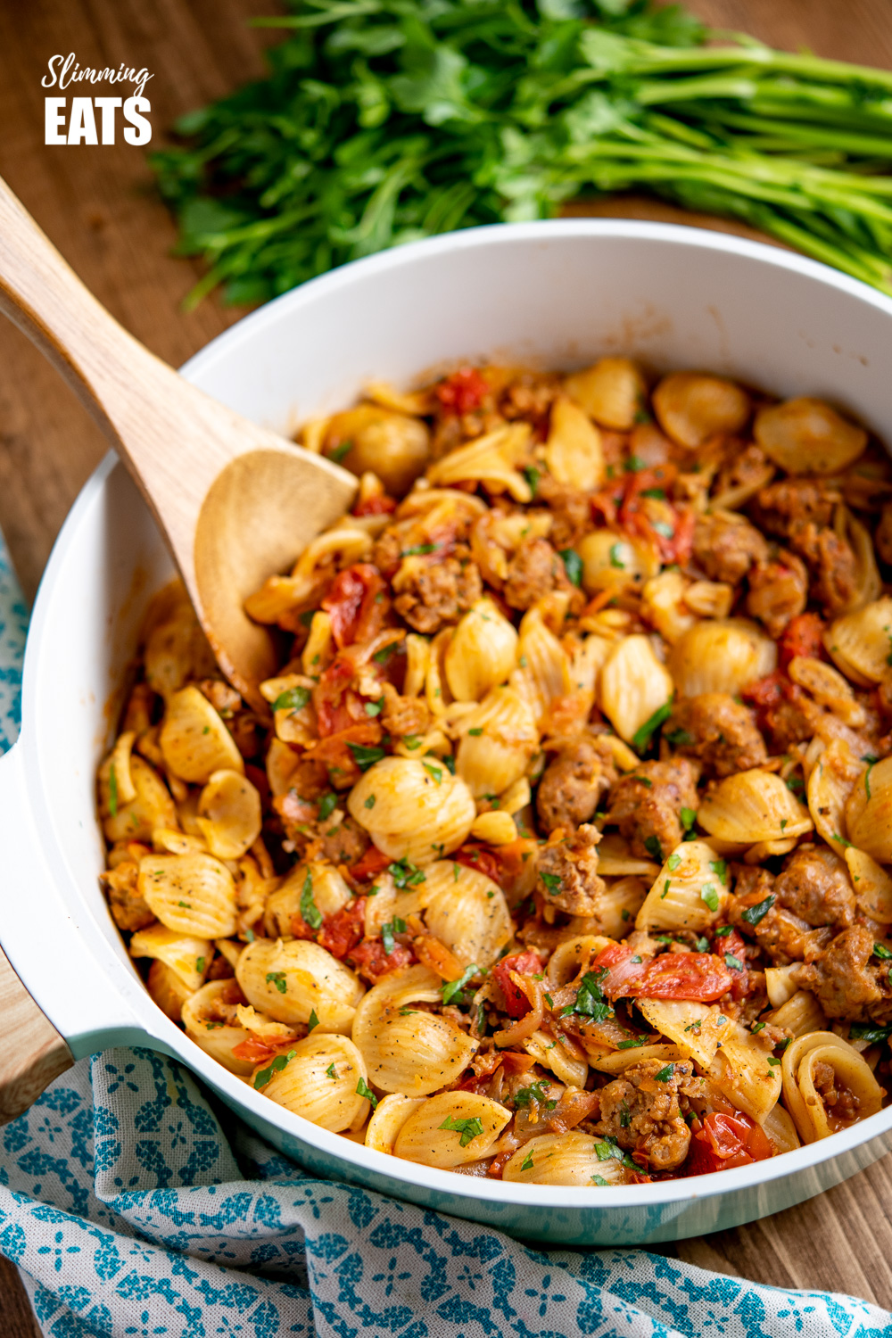 Sausage, Balsamic Tomatoes and Onion with Orecchiette in casserole pan with wooden spoon