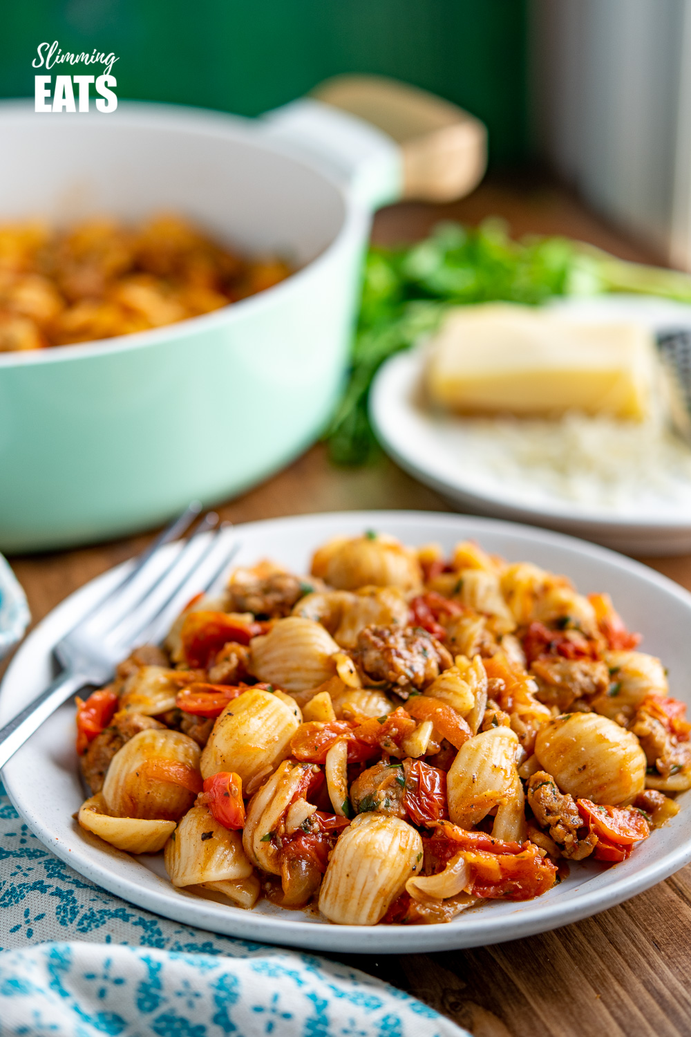 Sausage, Balsamic Tomatoes and Onion with Orecchiette on white plate with fork
