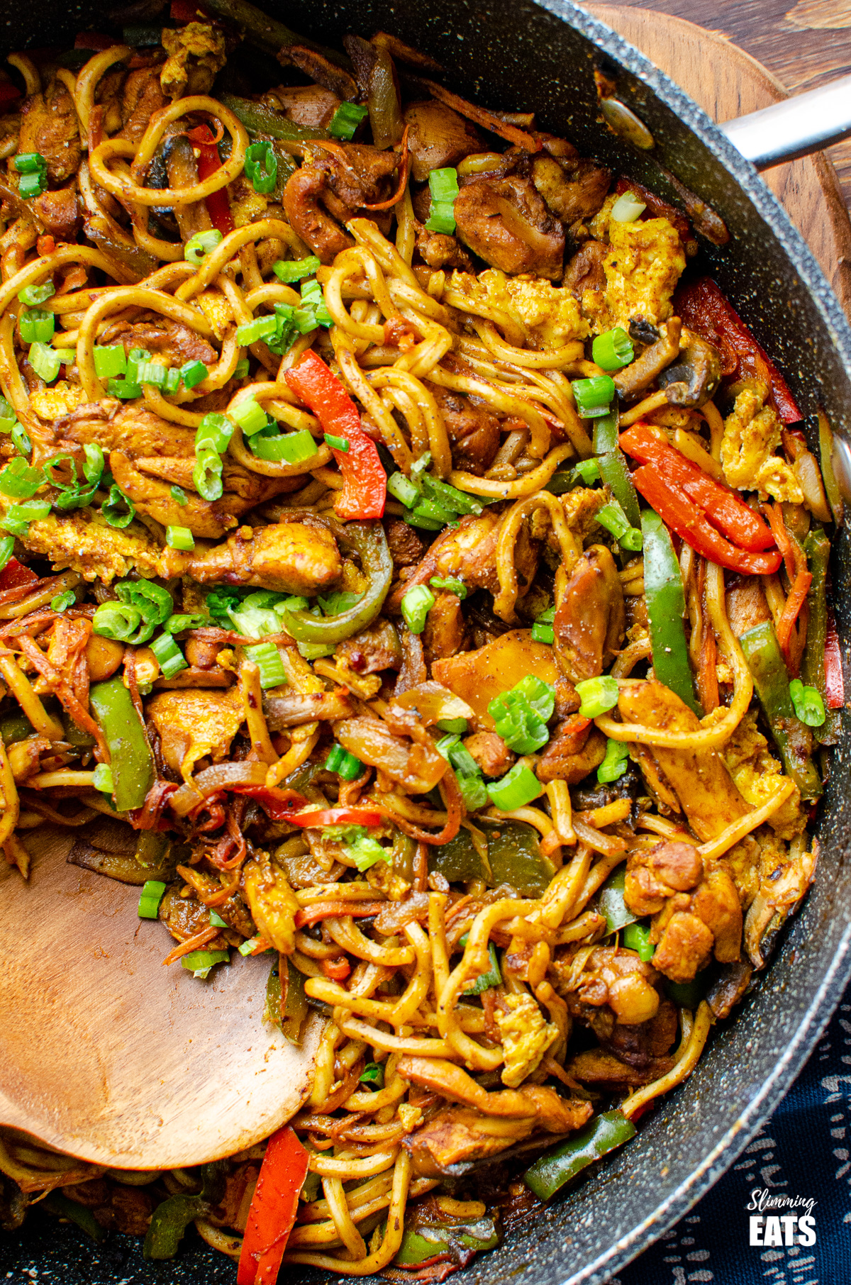 close up of Delicious Singapore Chicken Noodles in a frying pan with wooden spoon
