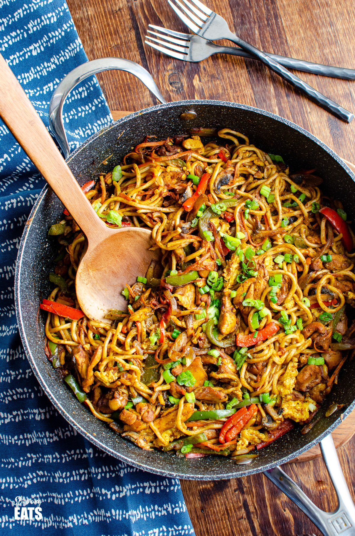 Delicious Singapore Chicken Noodles in a frying pan with wooden spoon