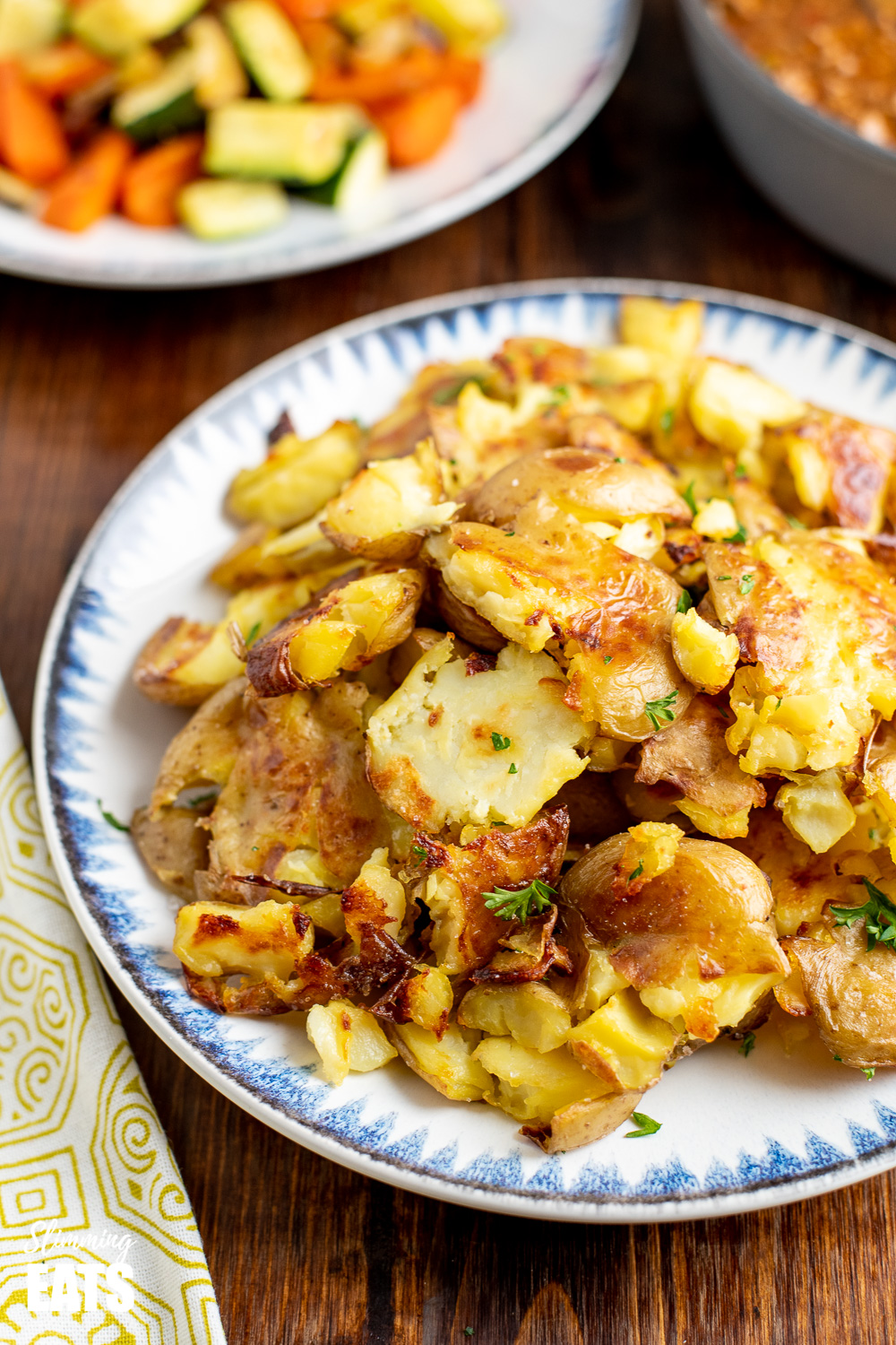 crushed roast potatoes on white plate with vegetables in background