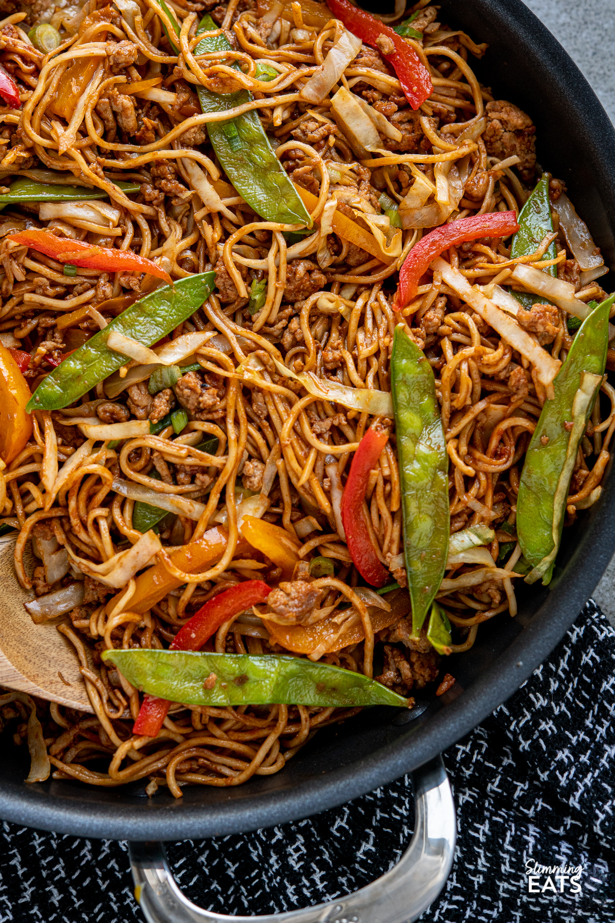 close up of Hoisin Pork and Noodles  in black two handled frying pan