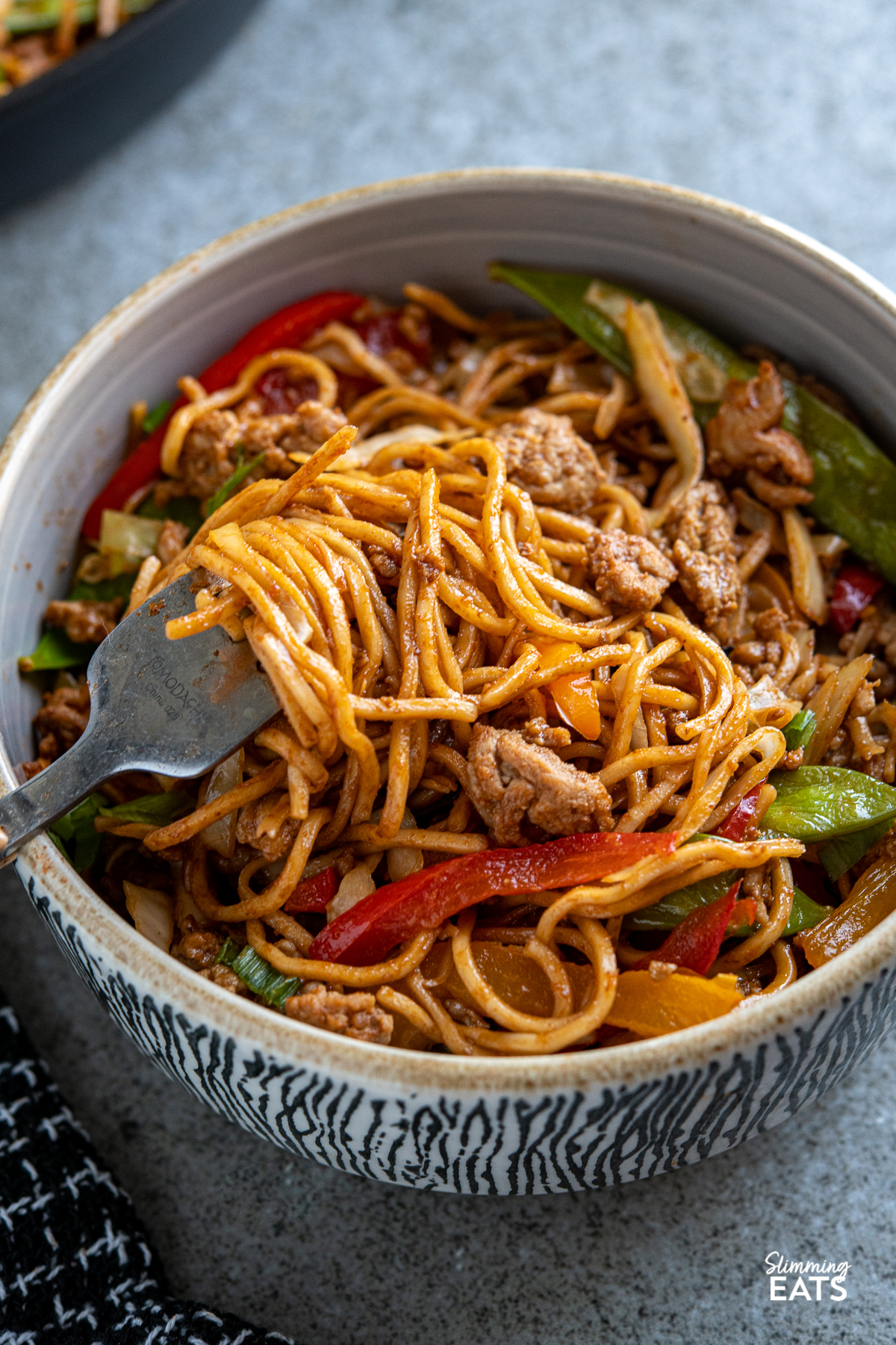 fork twisting noodles with hoisin pork and veggies from a grey bowl