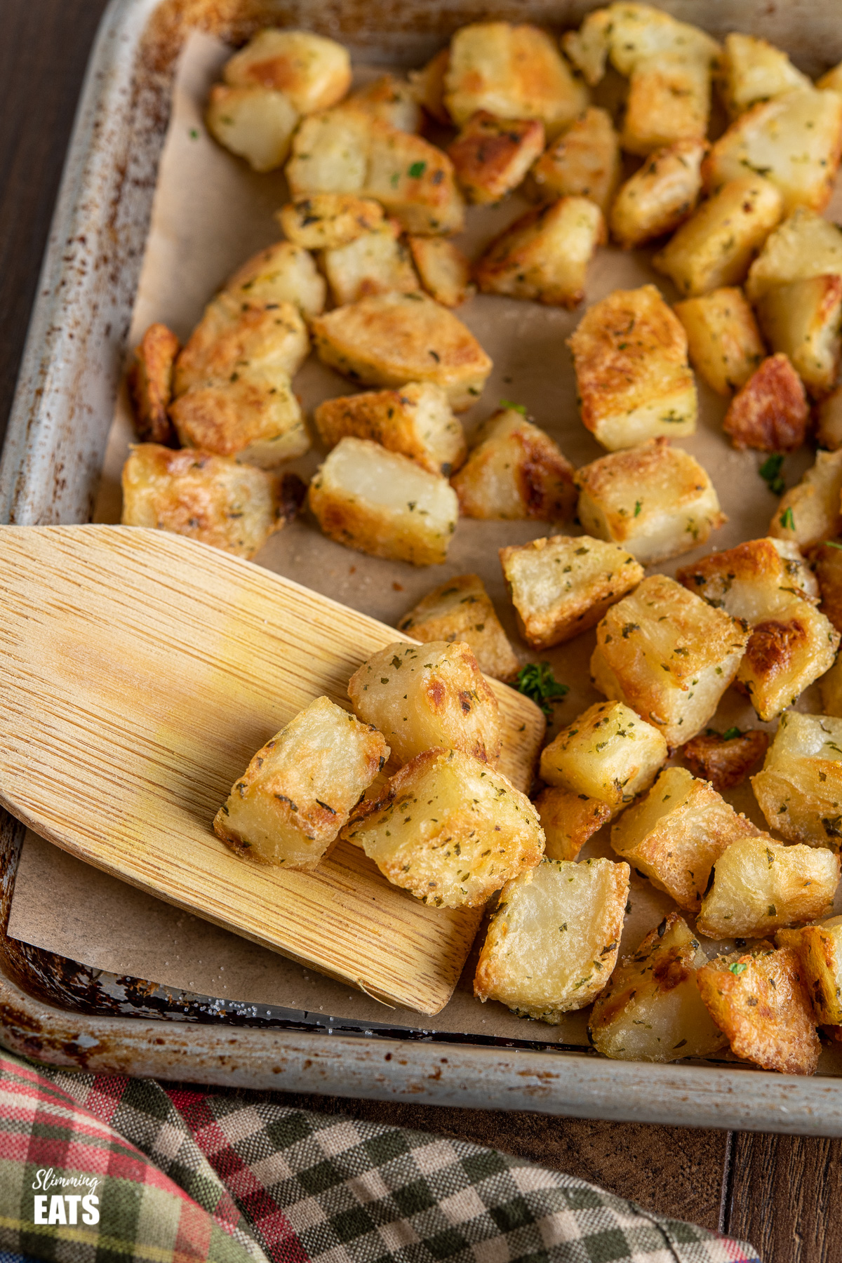 close up of Garlic and Herb Roasted Potatoes on a wooden spatula from baking tray