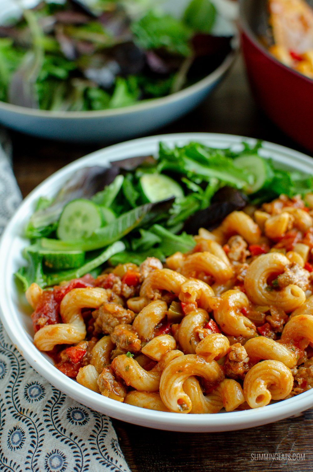sausage and tomato pasta in white bowl with mixed baby greens and cucumber