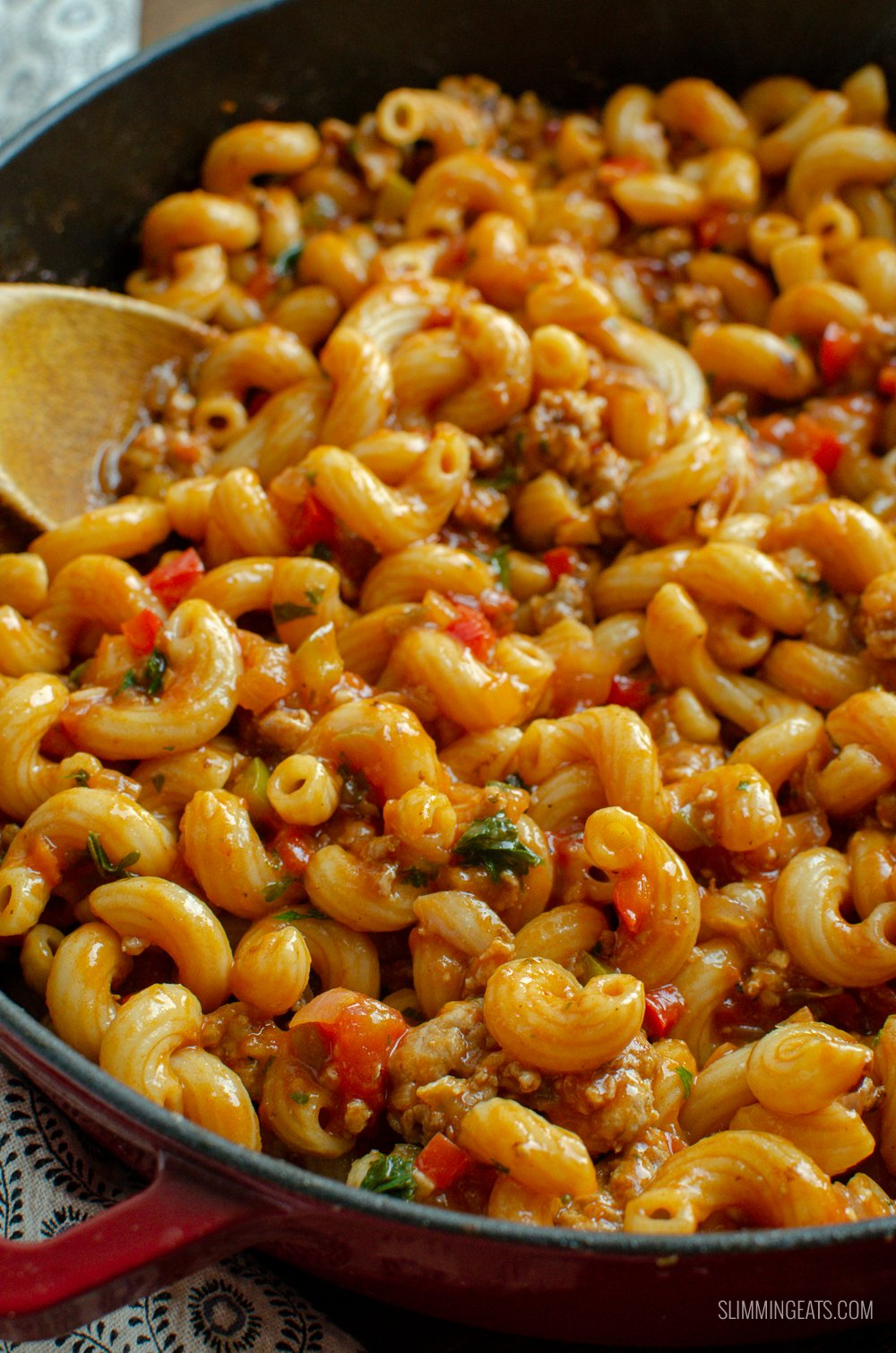sausage and tomato pasta with wooden spoon