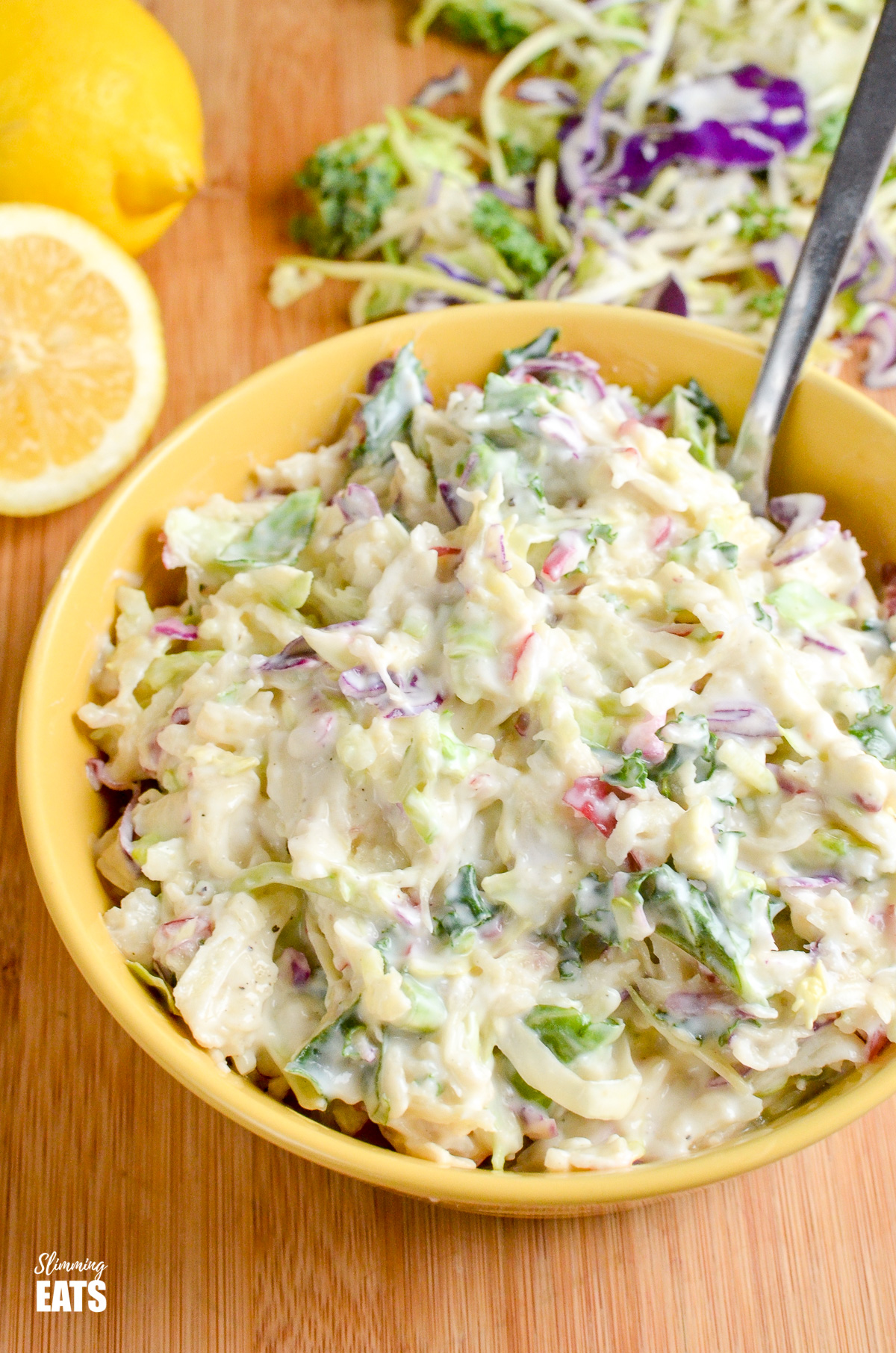 Sweet Tangy and Creamy Apple Coleslaw in a yellow bowl with scattered halved lemons and slaw