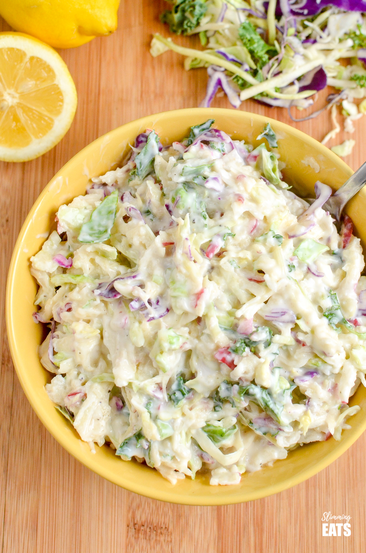 Sweet Tangy and Creamy Apple Coleslaw in a yellow bowl with scattered halved lemons.