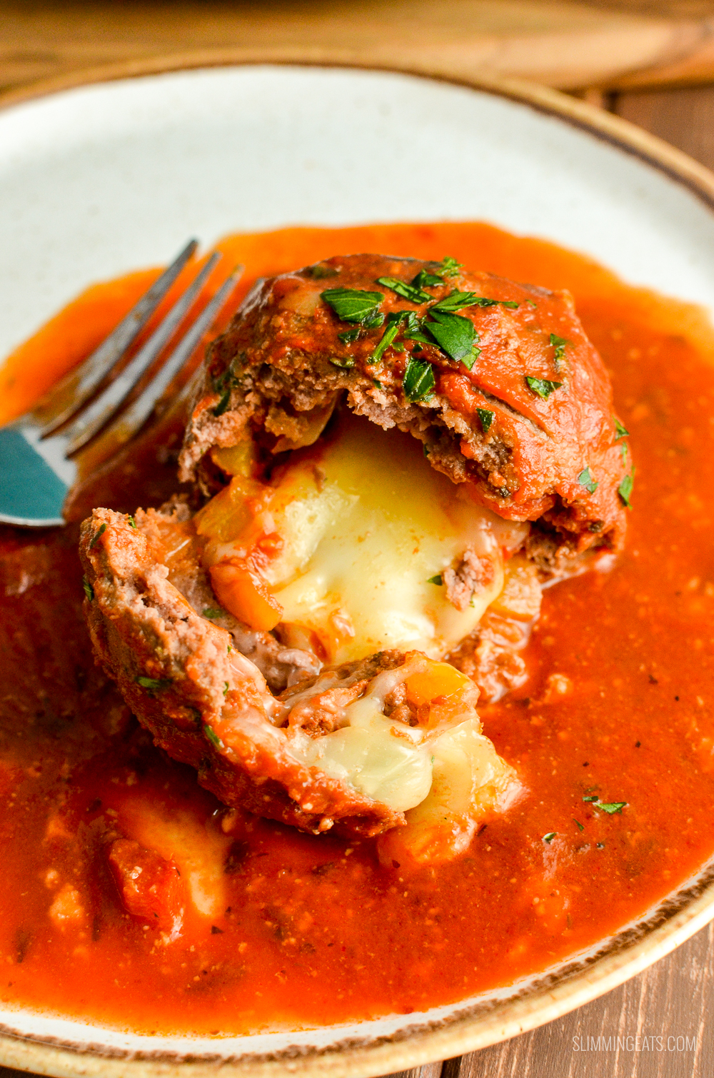 close up of broken open mega stuffed meatball with oozing melted mozzarella