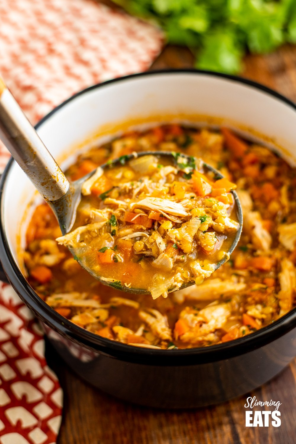 ladle of chicken and lentil soup from saucepan